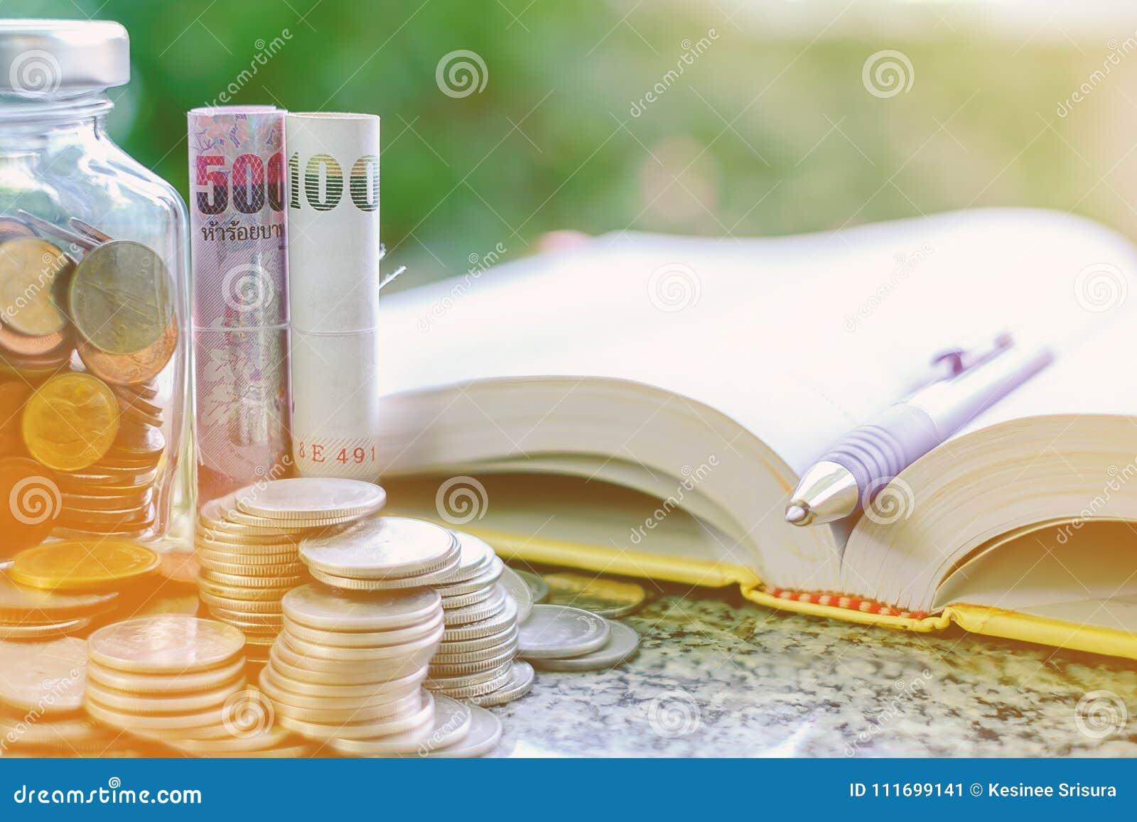 Куча монеток денег в и снаружи стеклянного опарника и тайские curren