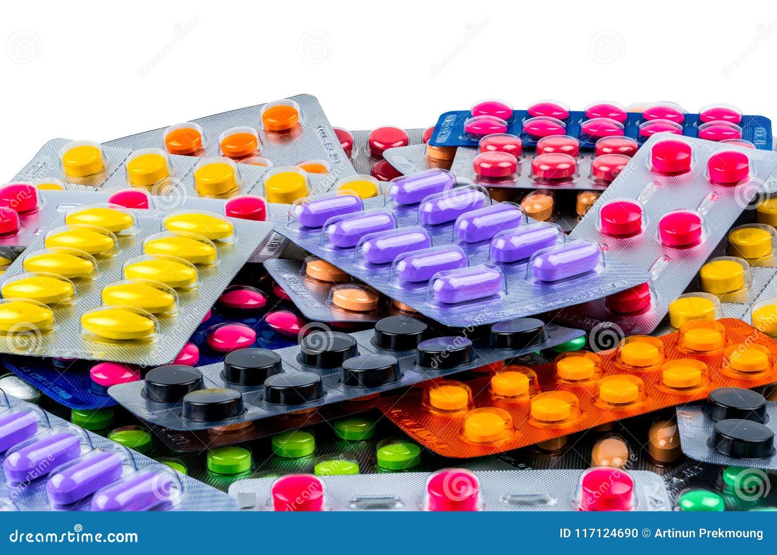 Куча пилюлек таблетки на белой предпосылке Желтые, фиолетовые, черные, оранжевые, розовые, зеленые пилюльки таблетки в пакете вол