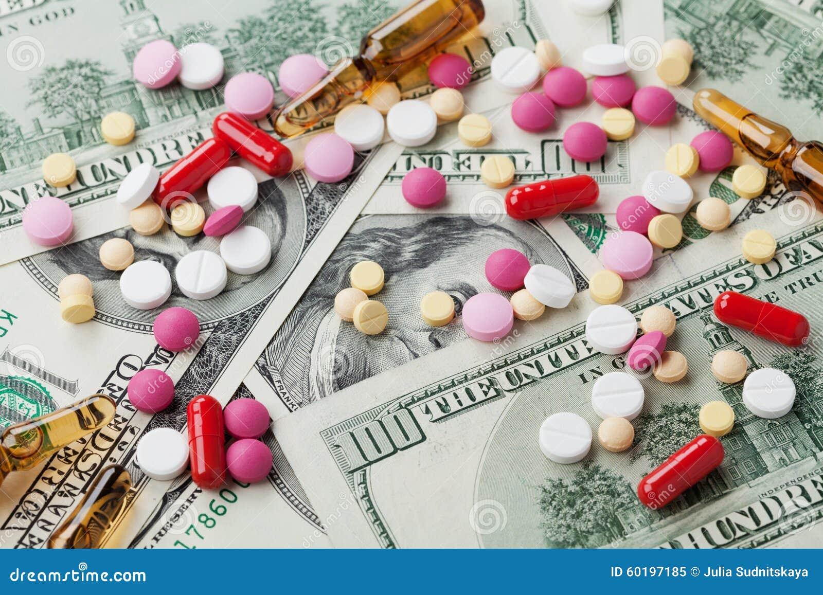 Куча фармацевтических пилюлек лекарства и медицины разбросала на деньги наличных денег доллара, продукт цены целебный и концепцию