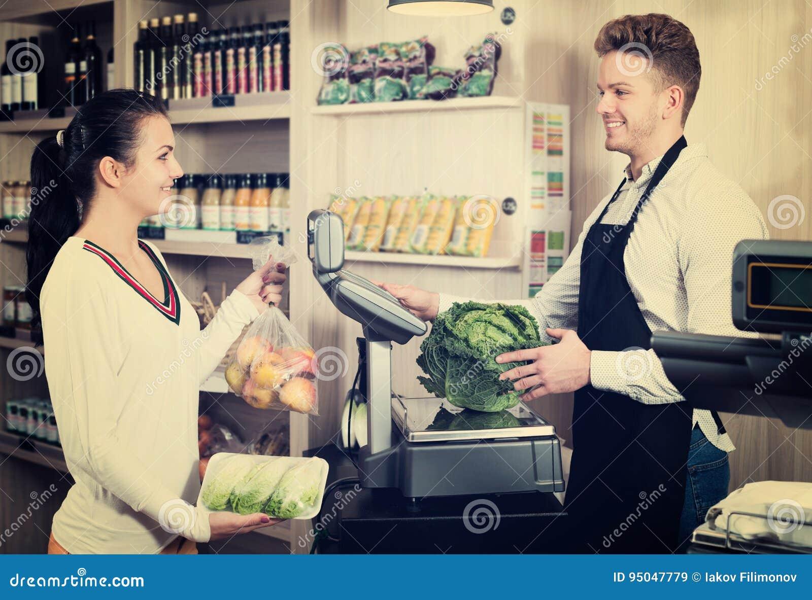 Клиент порции продавца человека для того чтобы весить приобретения