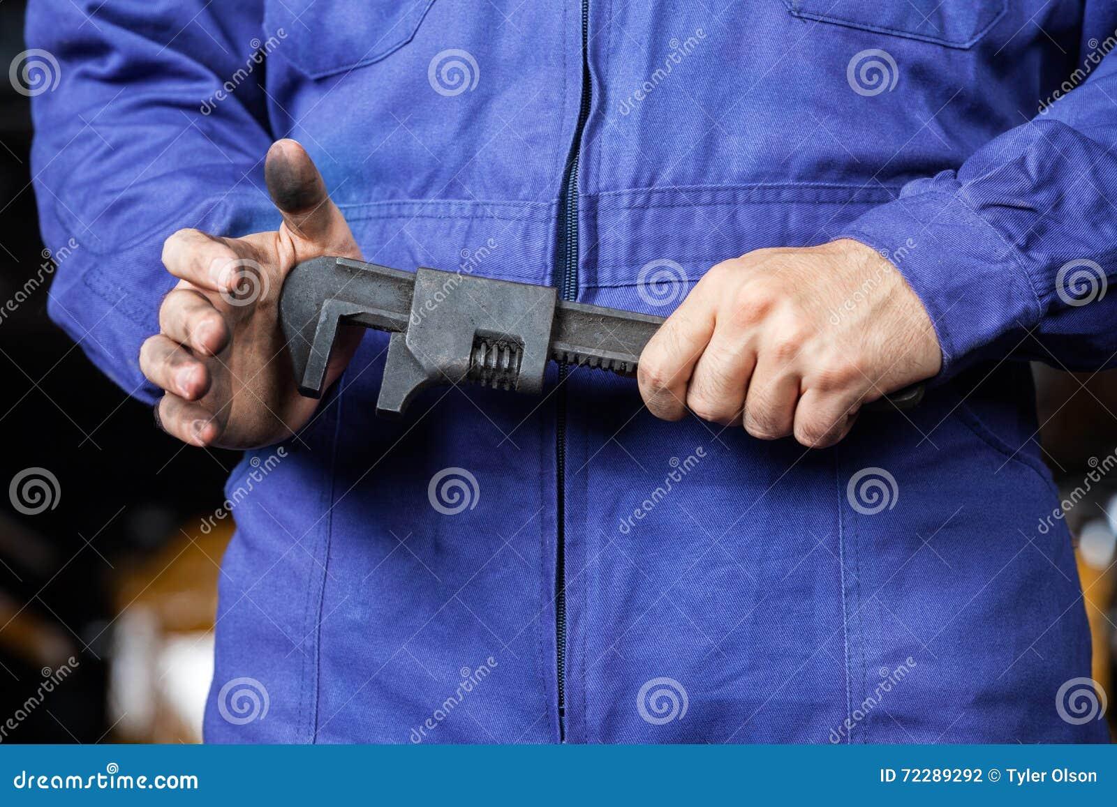 Download Ключ удерживания механика в ремонтной мастерской Стоковое Фото - изображение насчитывающей мужчина, управление: 72289292