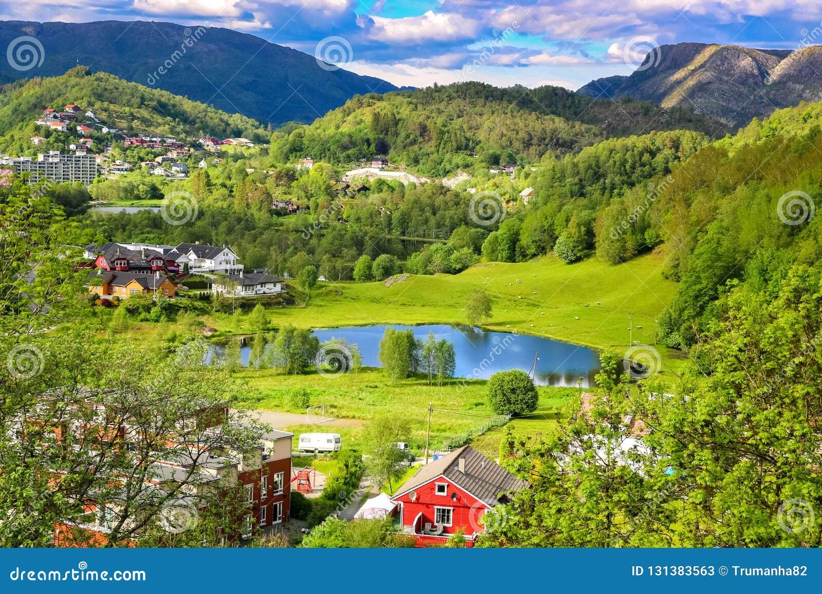 Ландшафт весны с обзором спокойной долины с зелеными лугами, прудом и красочными домами фермы в солнечном свете