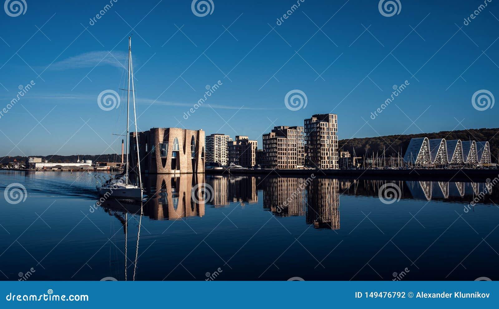 Ландшафт зданий около пристани Яхта на предпосылке новых зданий Голубой цвет