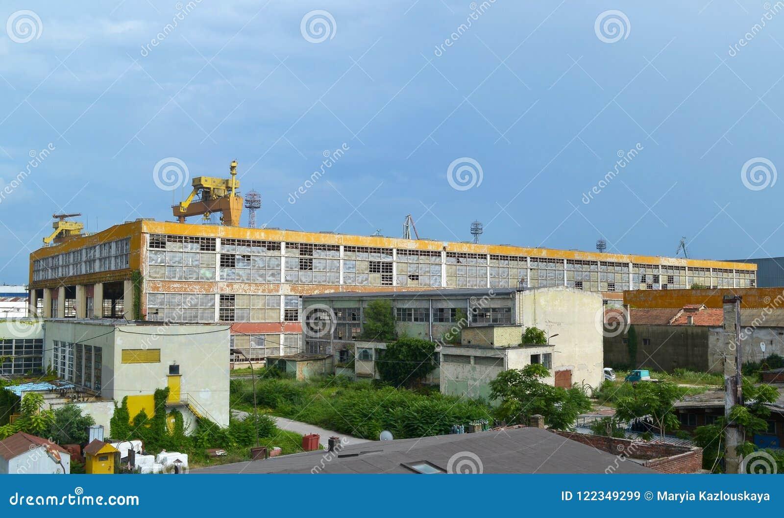 Ландшафт лета промышленный: голубое небо и большое покинутое промышленное желтое здание с сломленными окнами