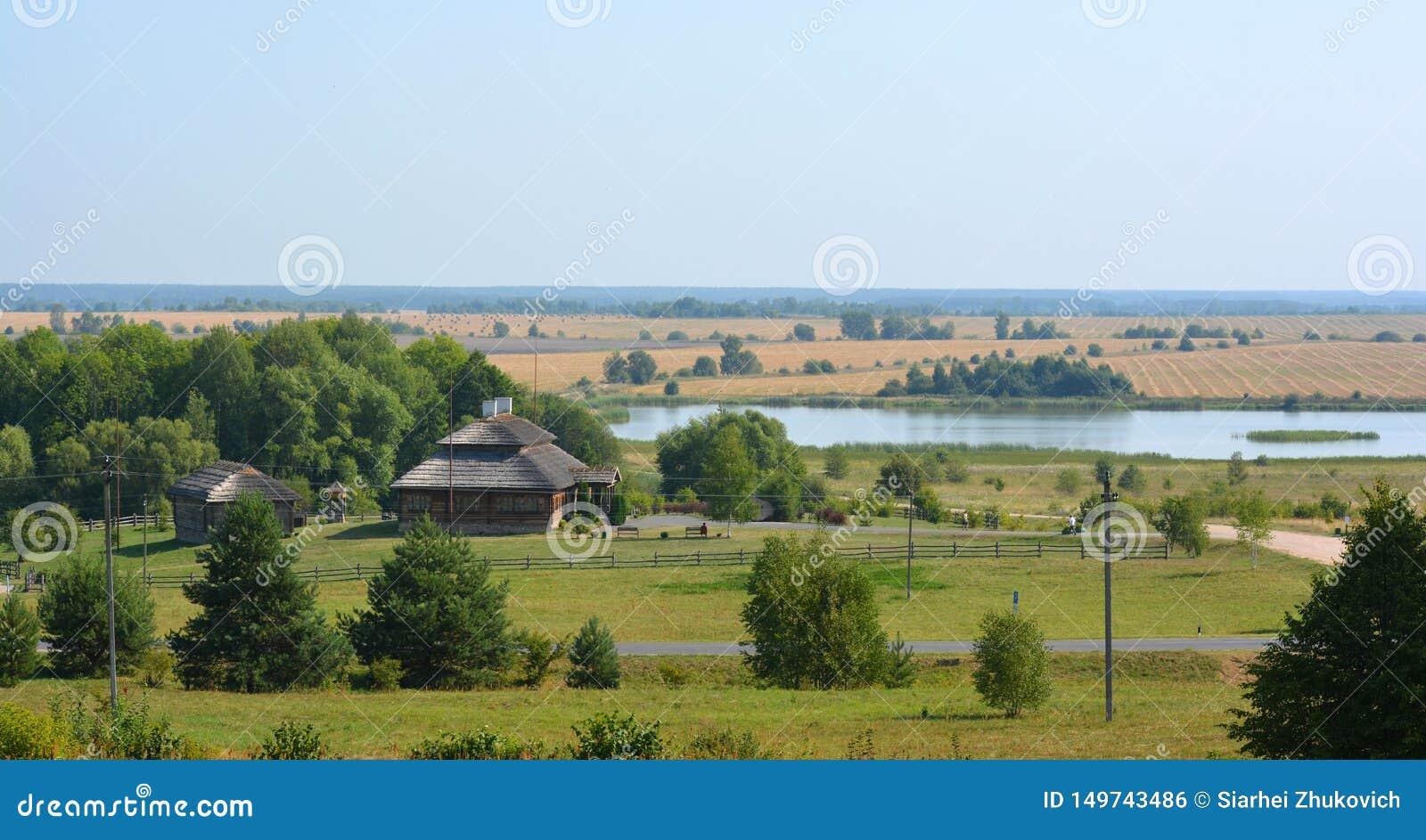Ландшафт лета сельский со старыми коттеджем и озером в Беларуси