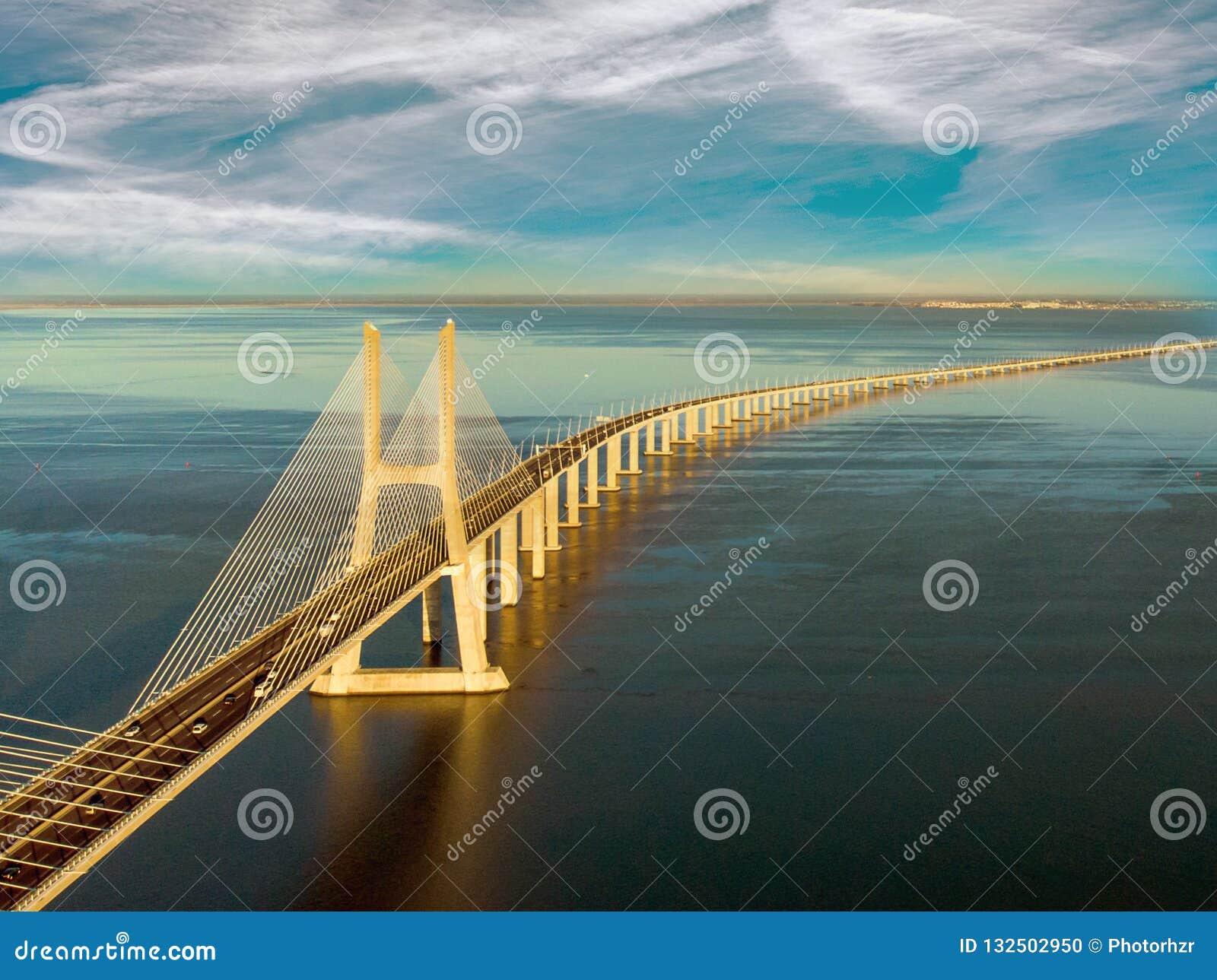 Ландшафт моста Gama Vasco da на восходе солнца Один из самых длинных мостов в мире Лиссабон изумительное туристское назначение