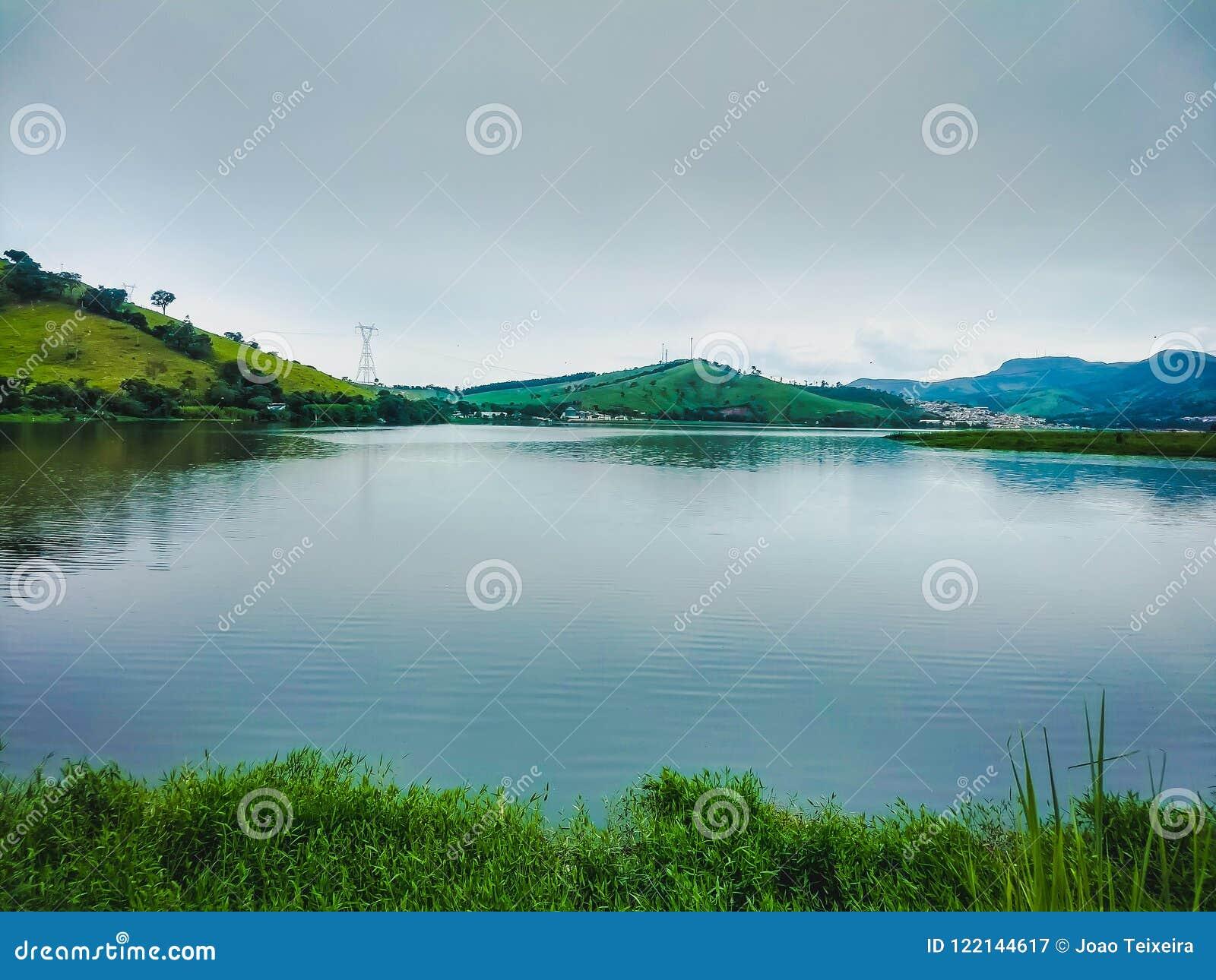 Ландшафт с озером открытого моря и с отражением деревьев которые вокруг, горы на заднем плане и травы в botto
