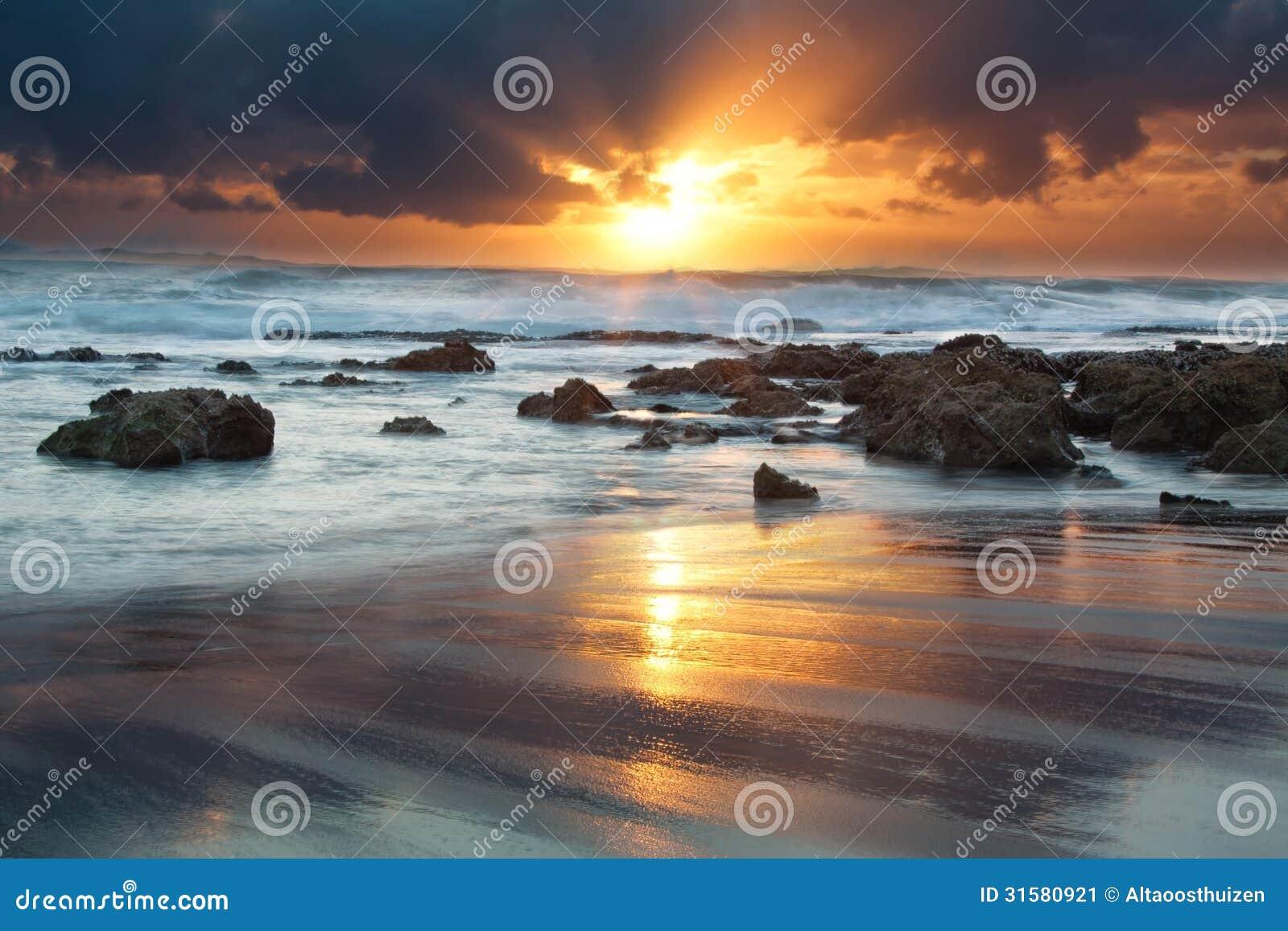 Ландшафт восхода солнца океана с облаками и утесами волн