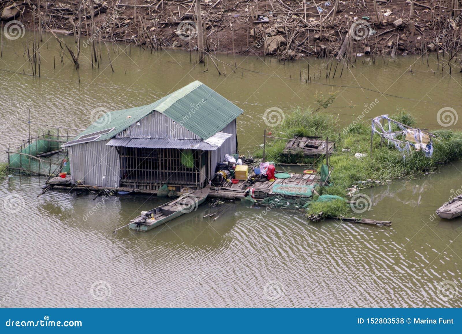 Лачуга дома в середине реки со шлюпкой и садом