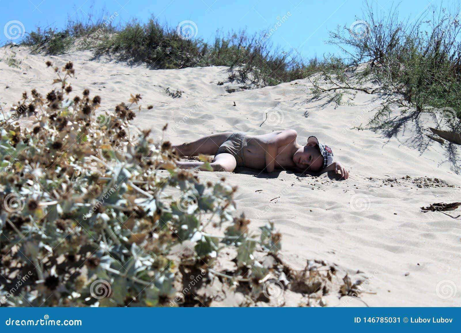 Лежать красивого младенца уставший на песке и загорает и отдыхать