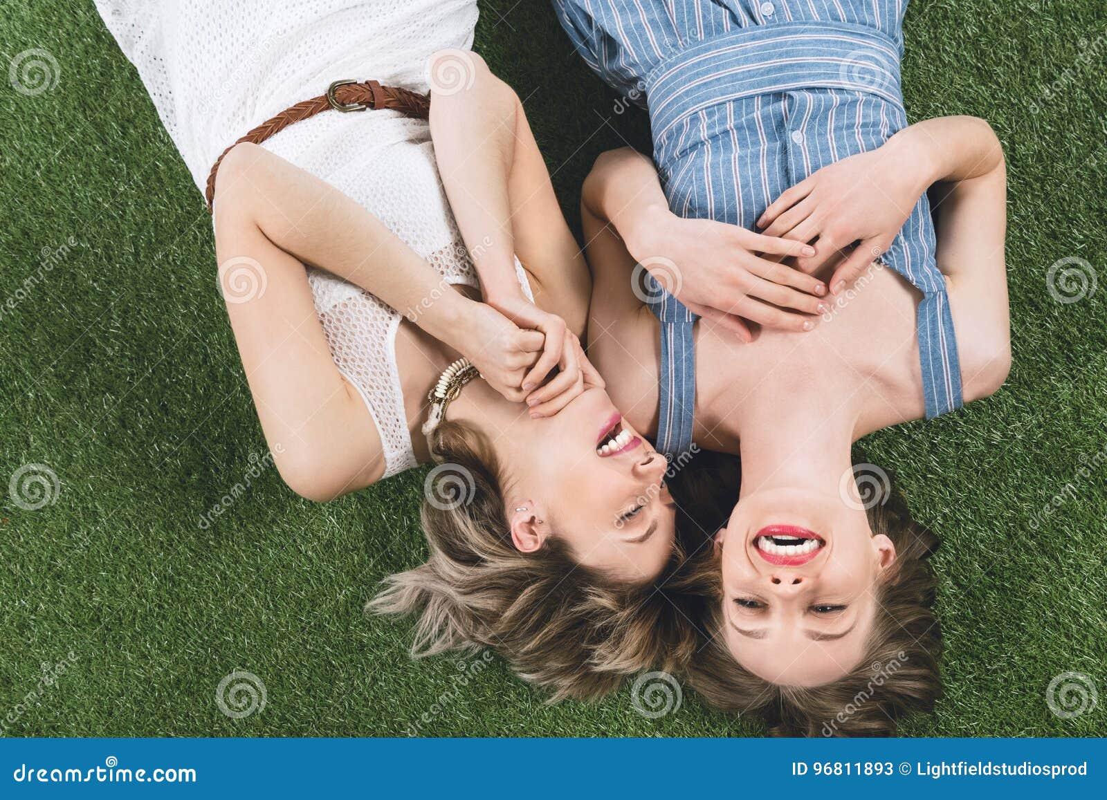 Лесбосские пары смеясь над пока лежащ совместно на траве