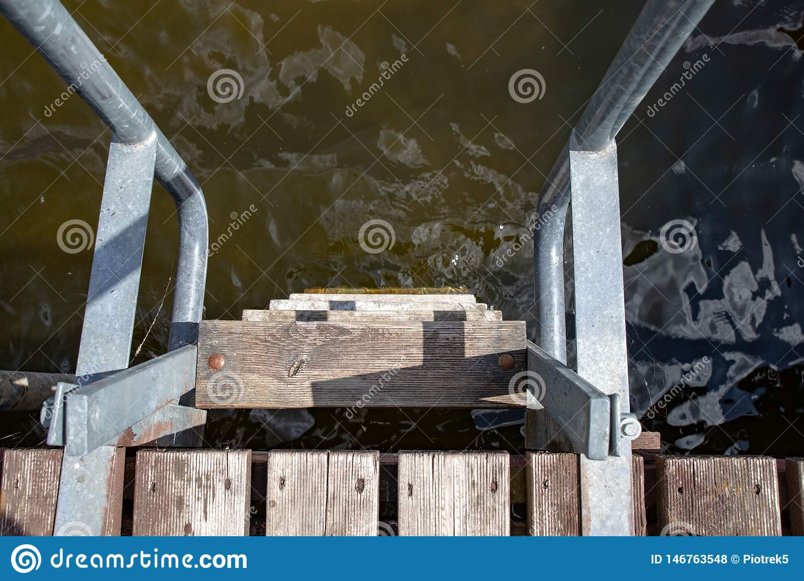 Лестница металла на деревянной пристани Спуск к воде на озере