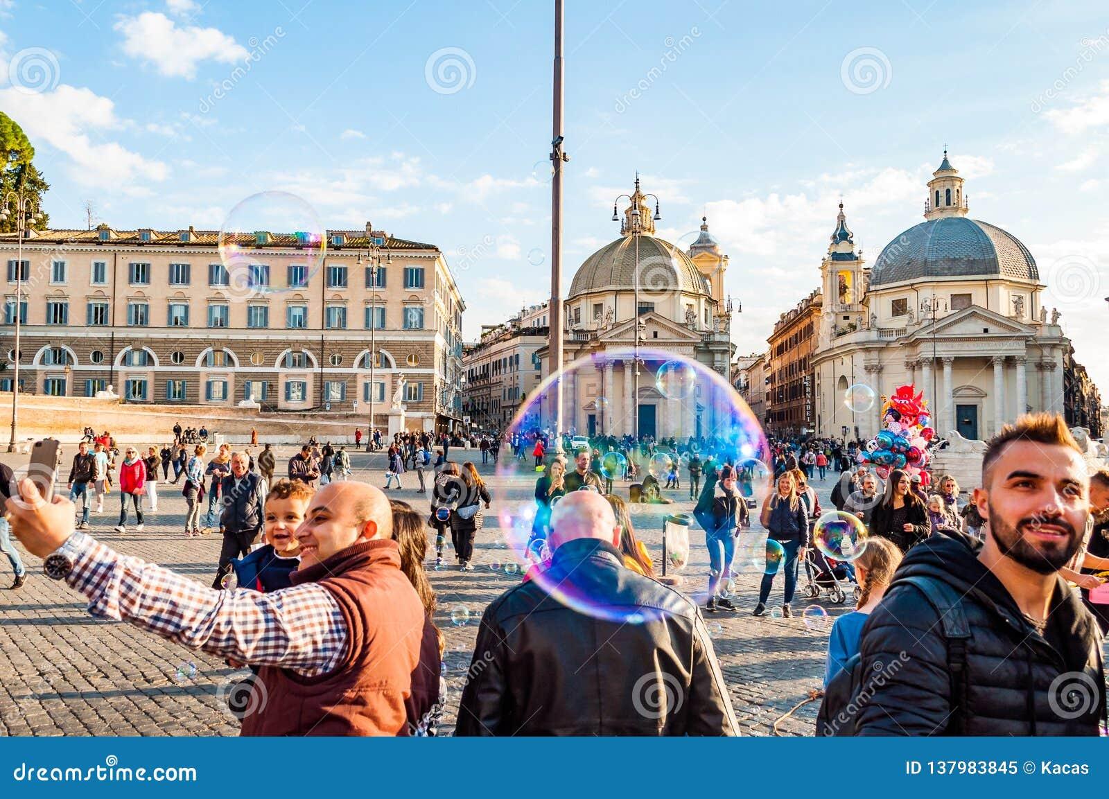 Летание пузырей мыла на Аркаде del Popolo, квадрате людей в Риме полном счастливых положительных людей, туристов и locals с римск