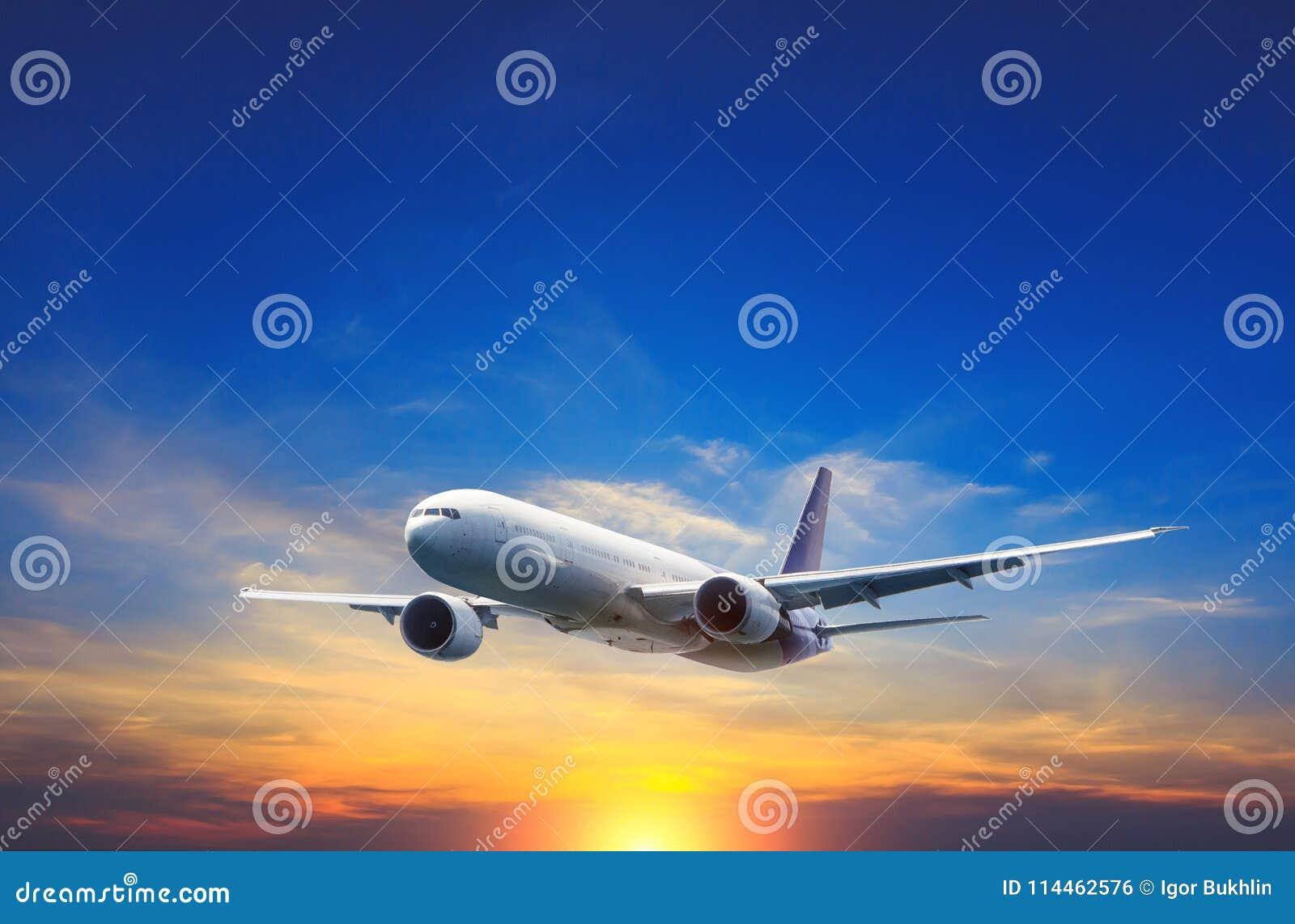 Летание самолета пассажира над облаками ночи и изумительным небом на заходе солнца
