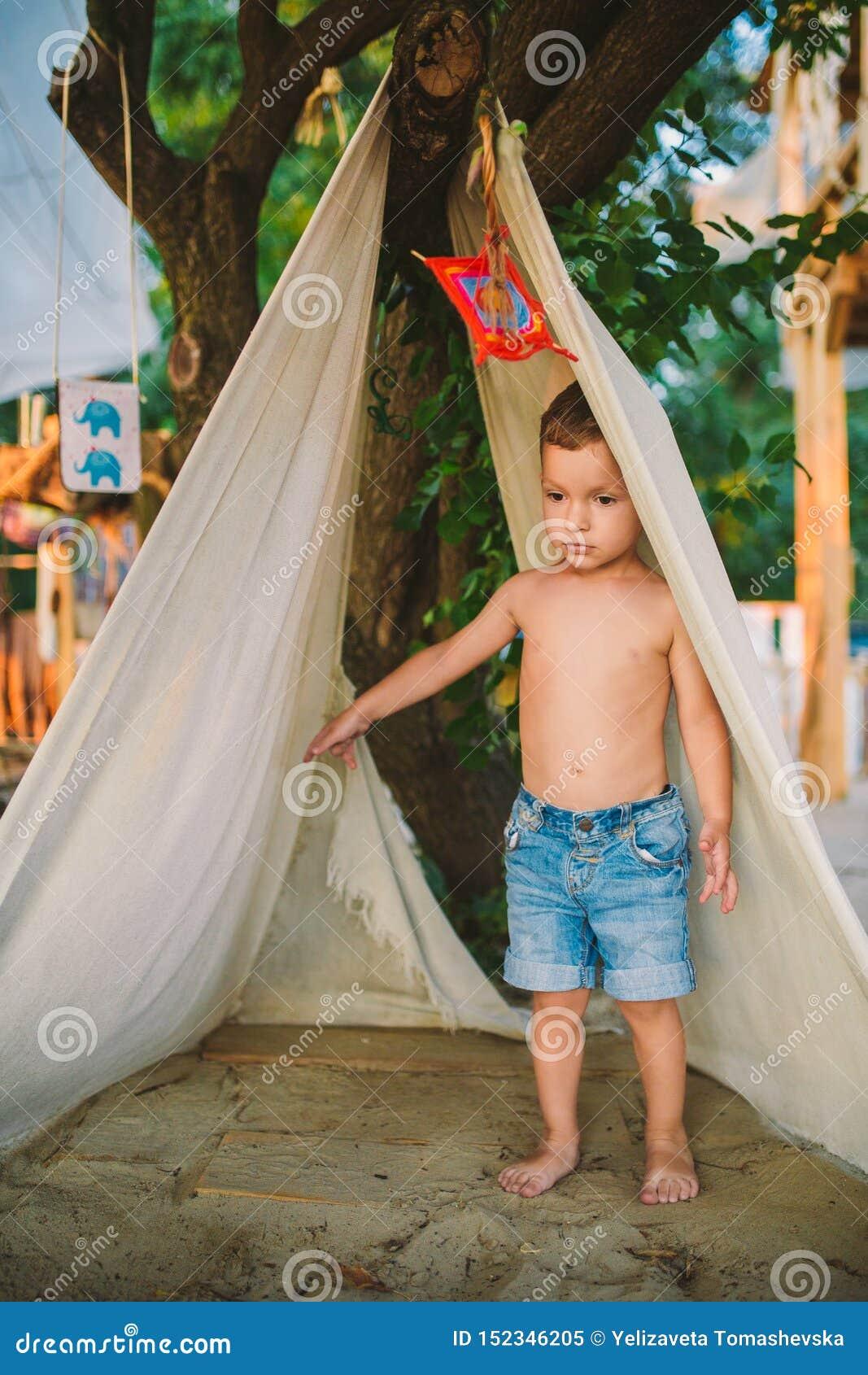 Летние каникулы темы, мальчик, кавказский ребенок играя в лесистом районе в парке на спортивной площадке во дворе ребенк в шатре
