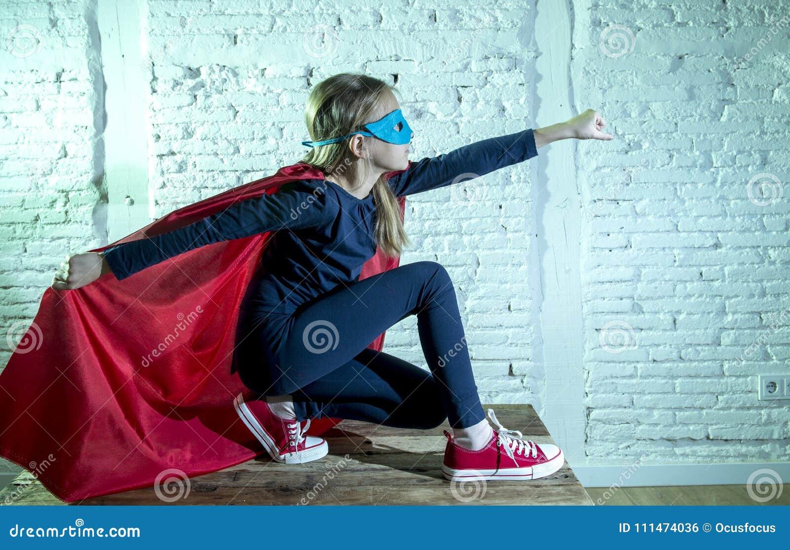Леты маленькой девочки девочки 7 или 8 старой выполняя счастливые и excited представляя нося крышку и маску в lo костюма фантазии