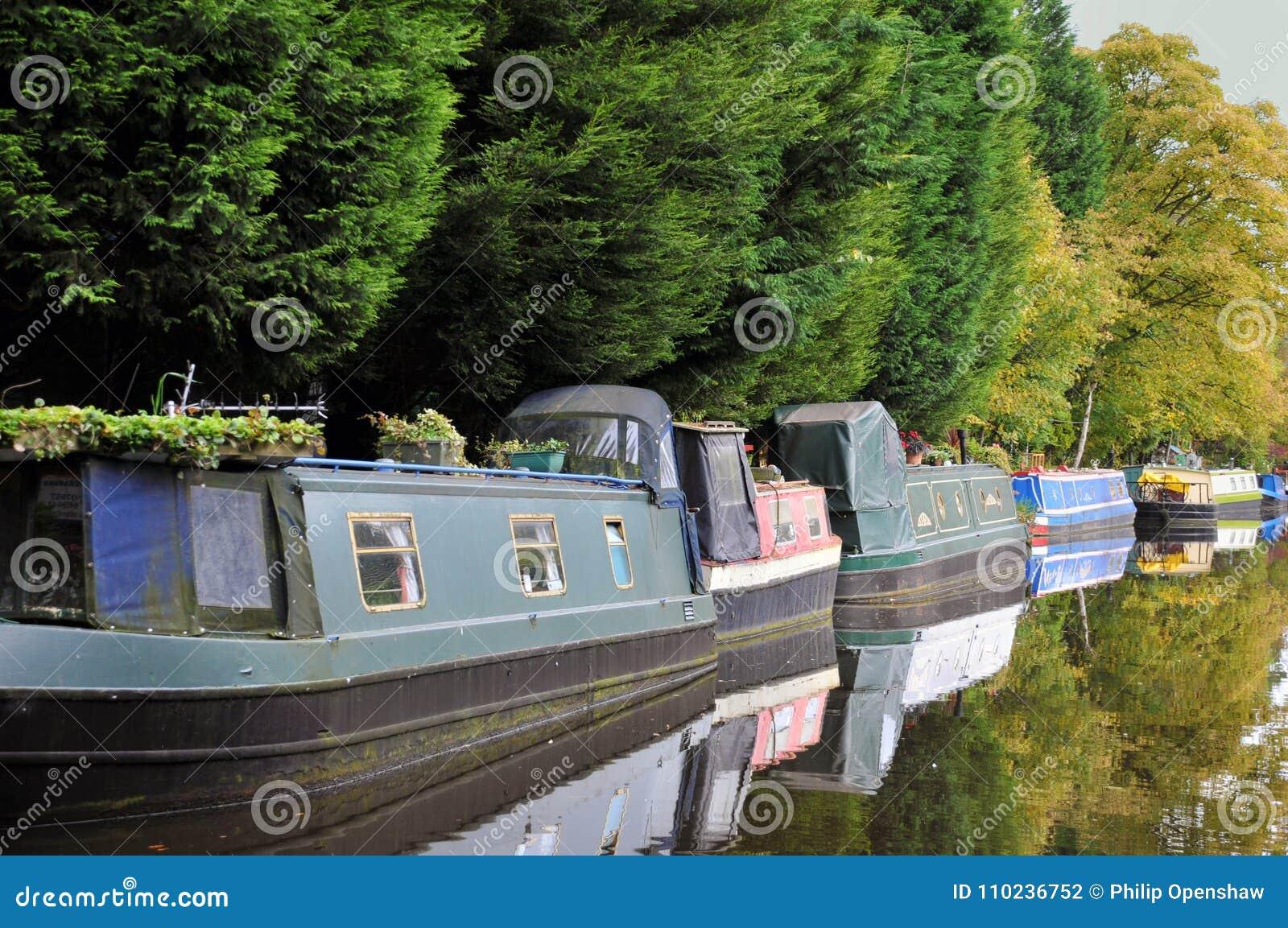 Линия традиционных узких шлюпок и плавучих домов причаленных вдоль канала с деревьями отразила в неподвижной воде в лете