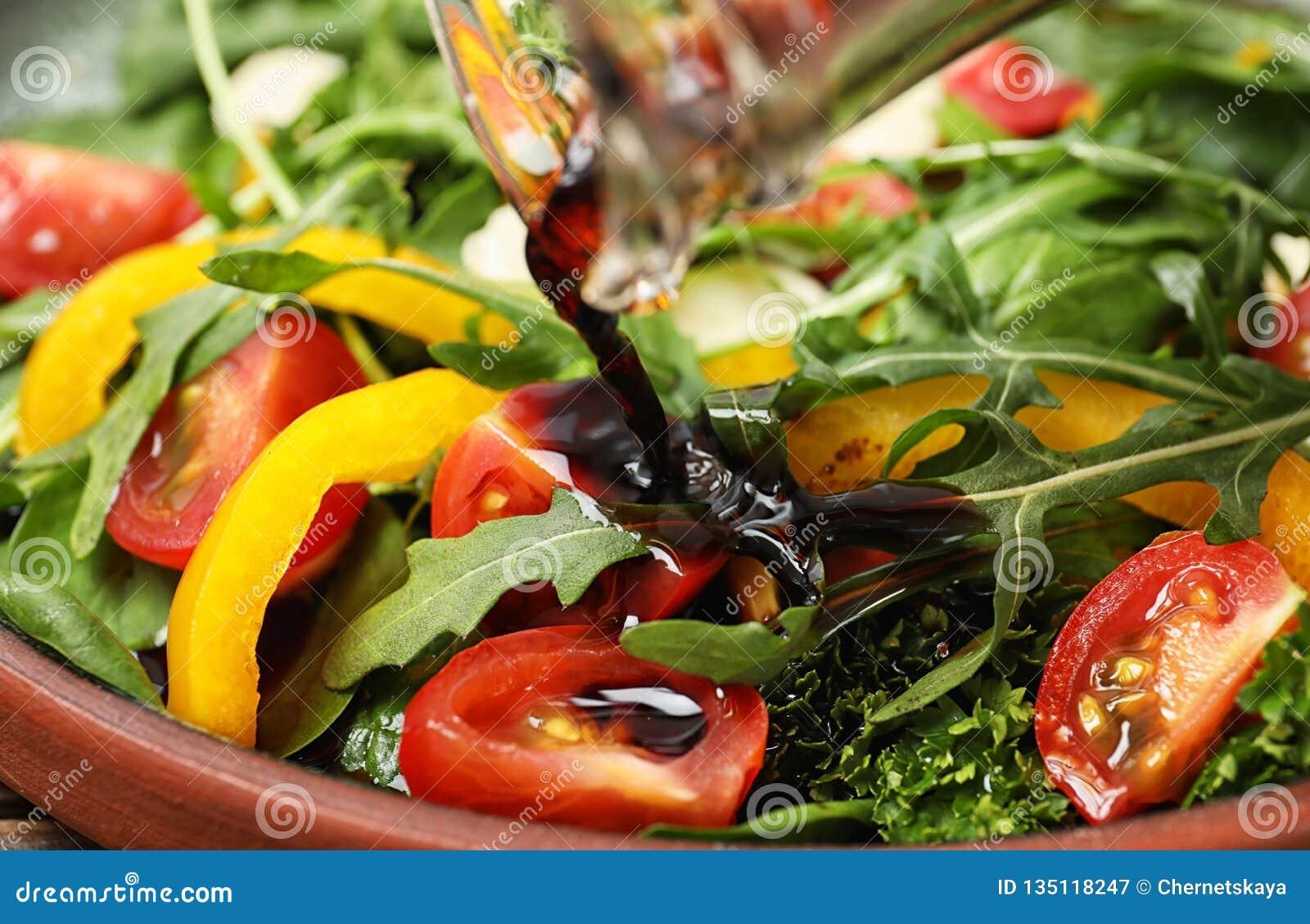 Лить бальзамический уксус к салату свежего овоща на плите