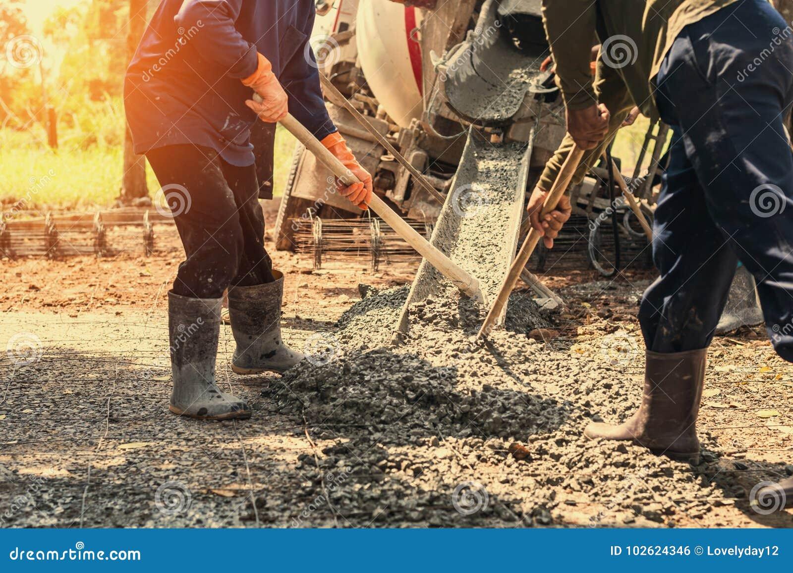 лить бетон с работником смешивает цемент на конструкции