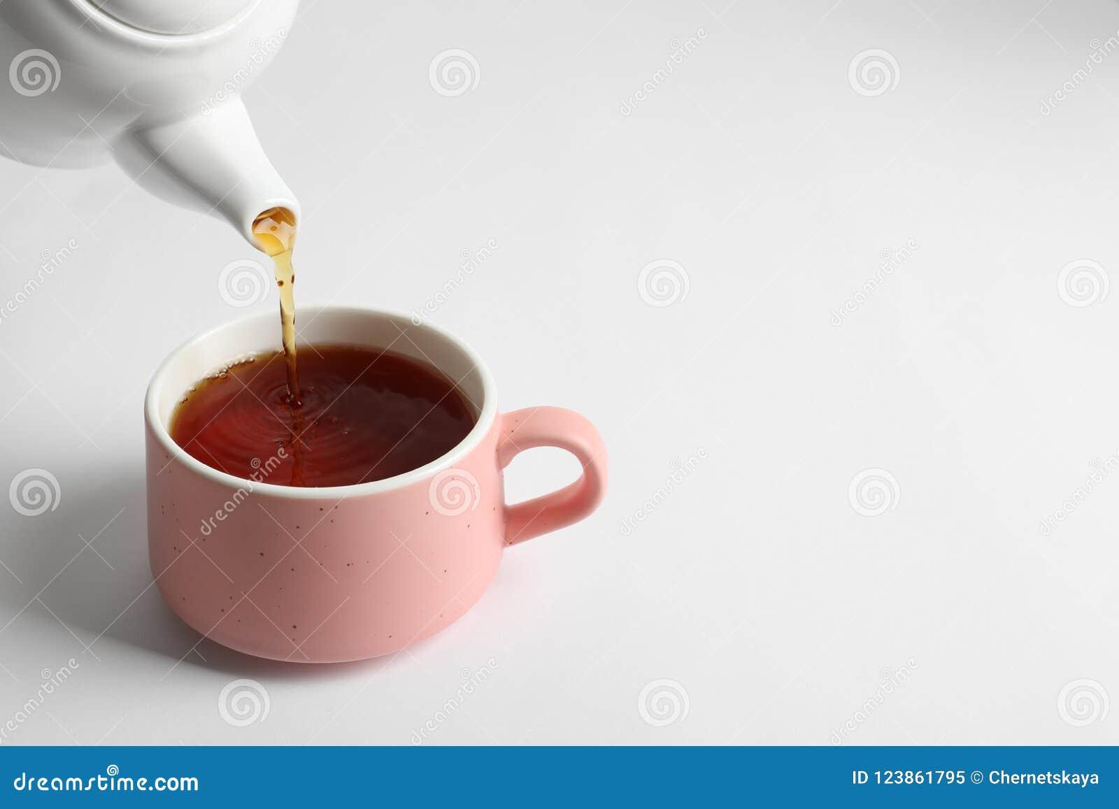 Лить горячий чай в керамическую чашку