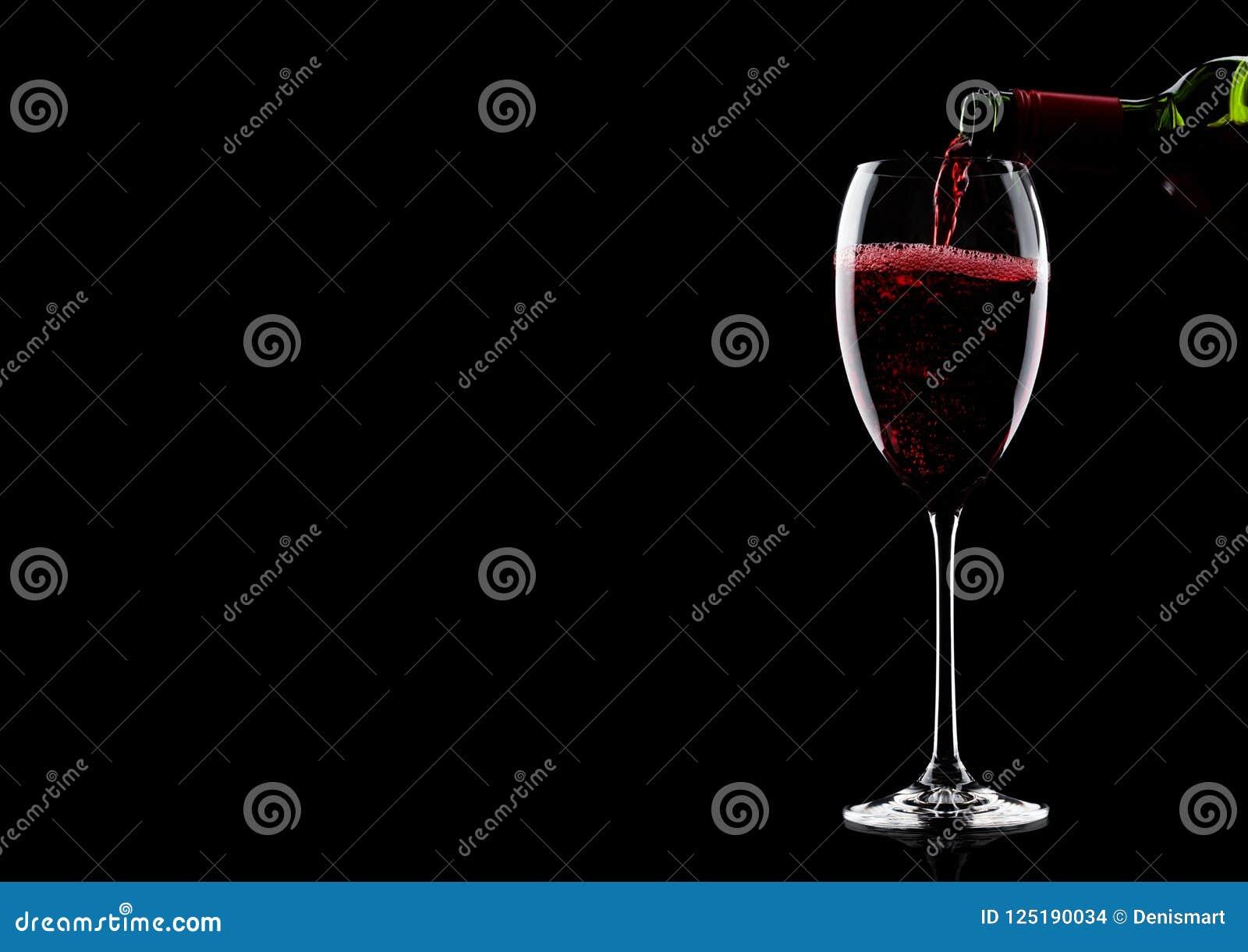 Лить красное вино от бутылки к стеклу на черноте с космосом для вашего текста