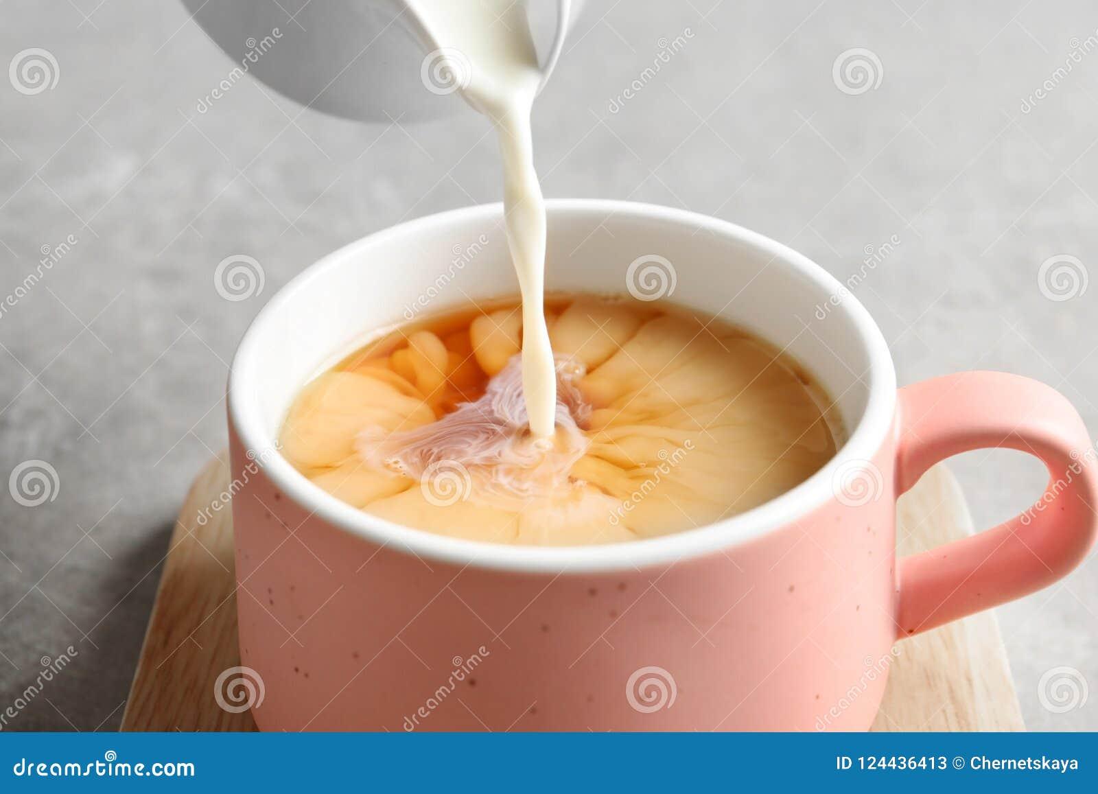 Лить молоко в чашку черного чая на серой таблице