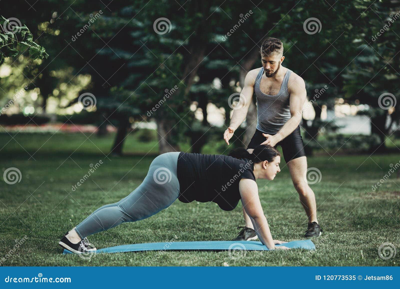 Личный тренер работая с его клиентом outdoors