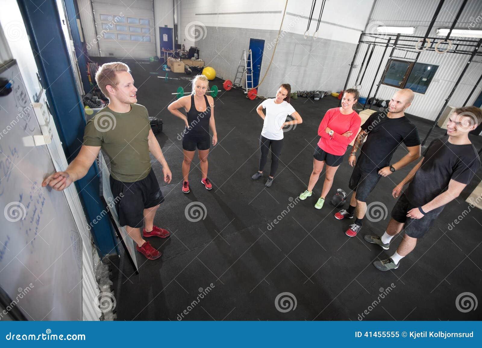Личный тренер учит его команде разминки фитнеса