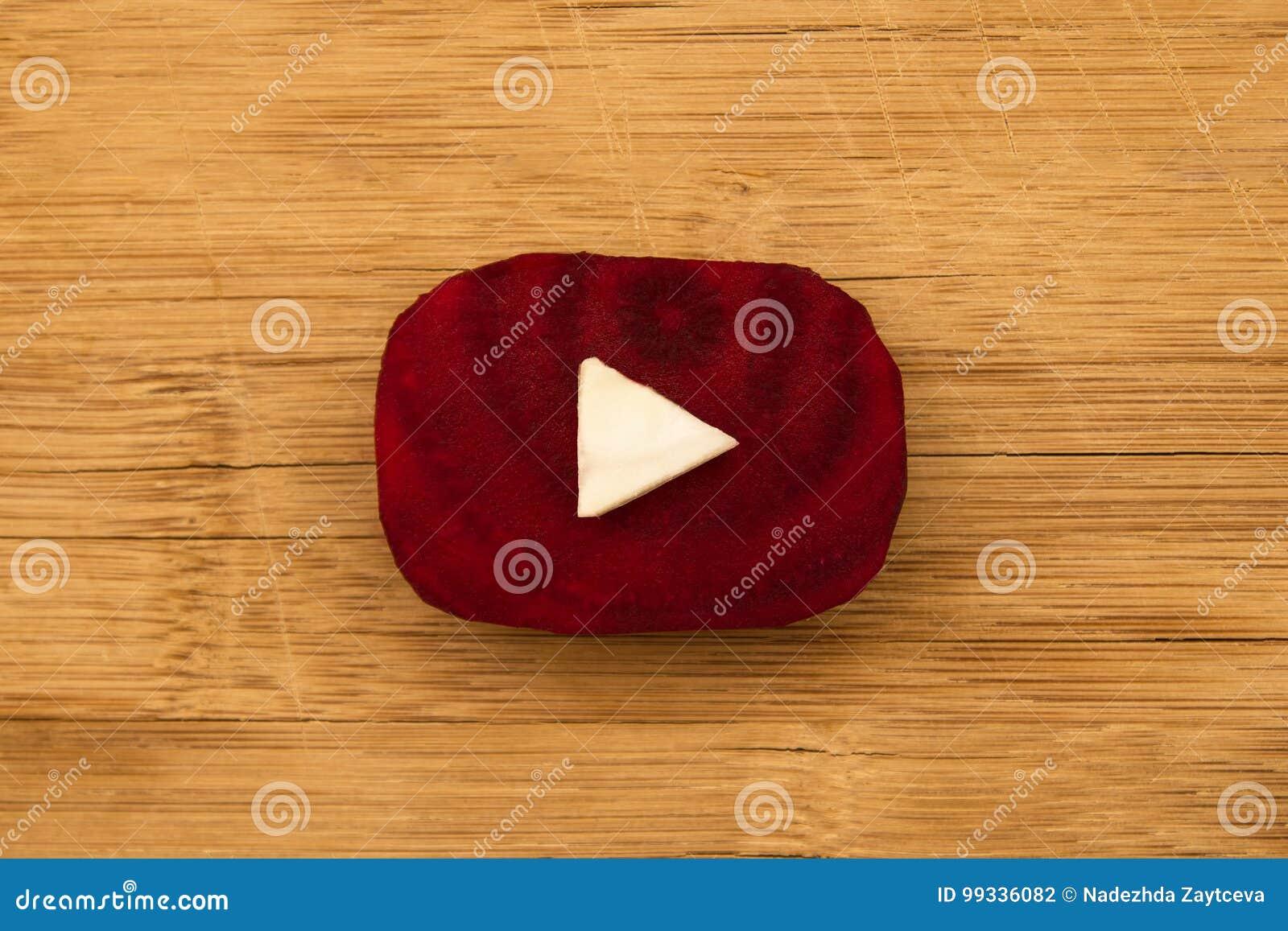 Логотип Youtube сделанный от частей бураков и капусты на деревянной предпосылке, взгляд сверху