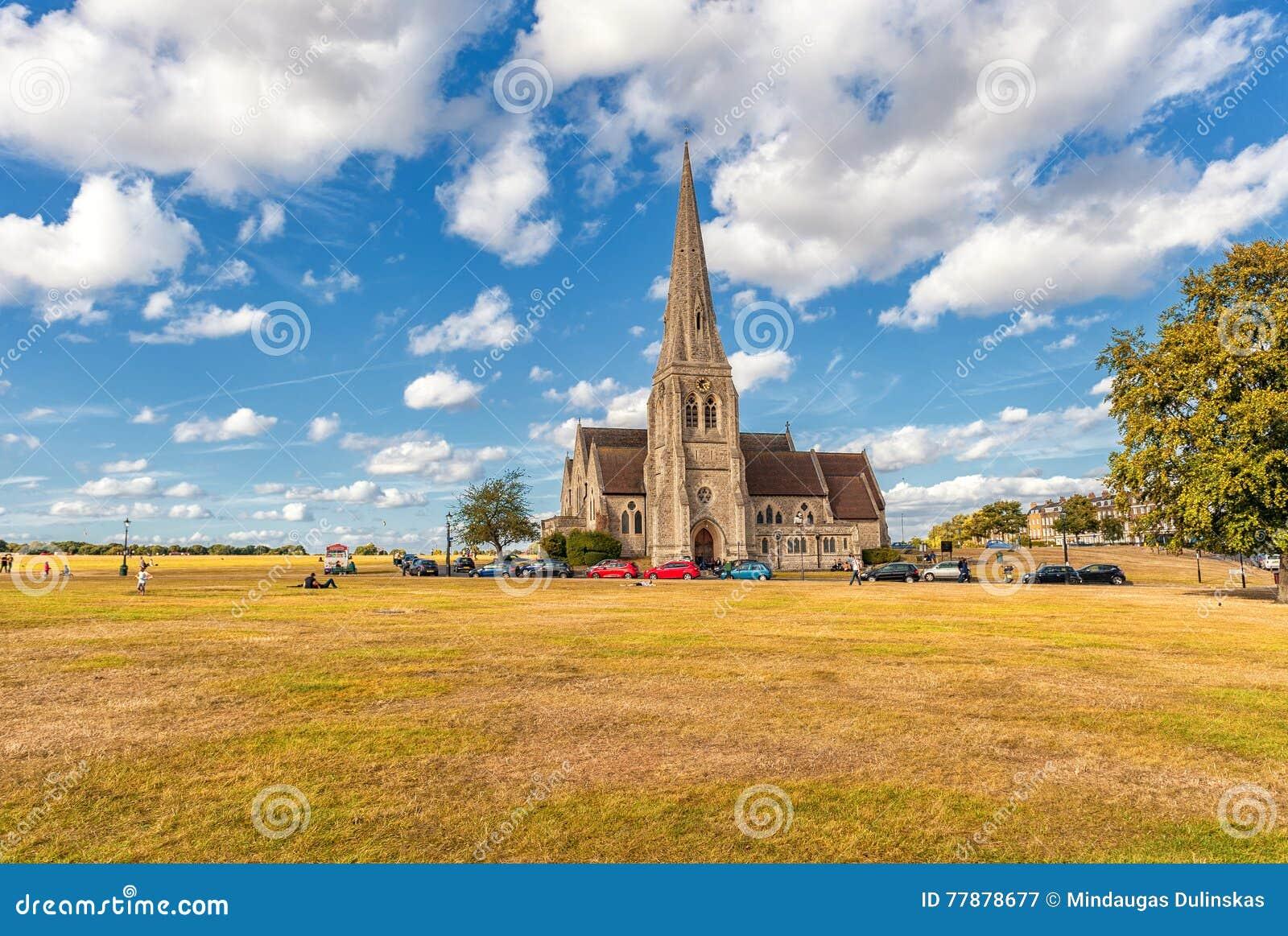 ЛОНДОН, АНГЛИЯ - 21-ОЕ АВГУСТА 2016: Blackheath с всеми Святыми Парк Гринвича с пасмурным голубым небом и зеленой травой