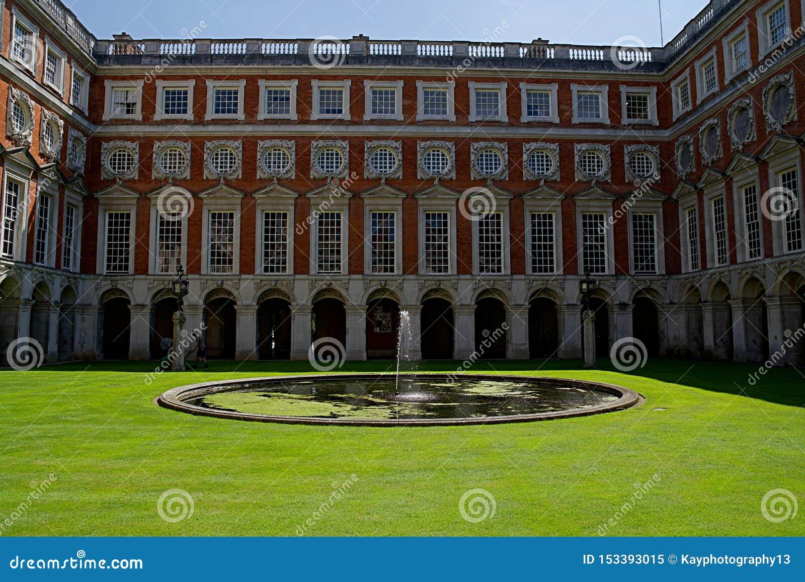 Лондон, Англия, 16-ое июля 2019: Взгляд двора дворца Хэмптон Корта с голубым небом