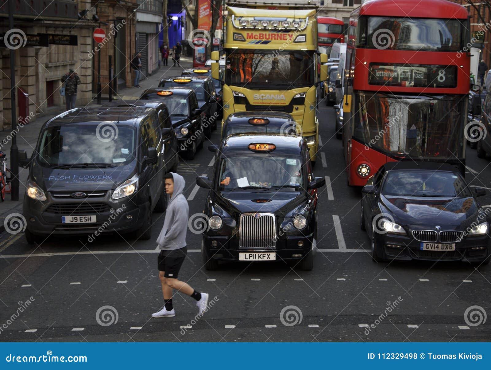Лондон, Англия: 8-ое марта 2018: Персона идя перед черной кабиной и другими автомобилями
