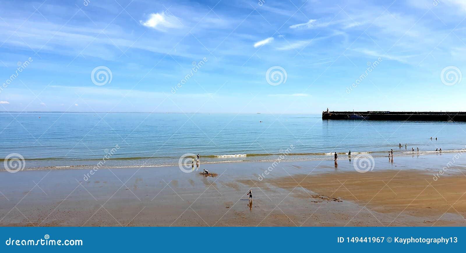 Лондон, Англия, Folkestone, Кент: 1-ое июня 2019: Туристы на солнечных песках приставают наслаждаться к берегу красивой солнечнос