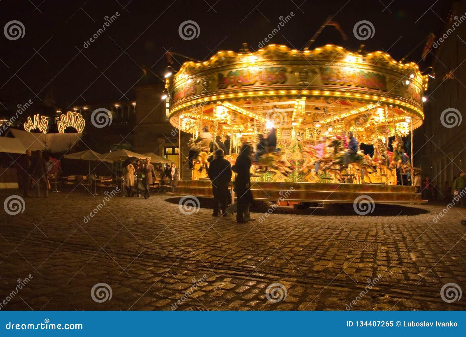 Лондон, Великобритания - 25-ое ноября 2006: Люди идя вокруг и наблюдая carousel загоренный в вечере на Ковент Гардене