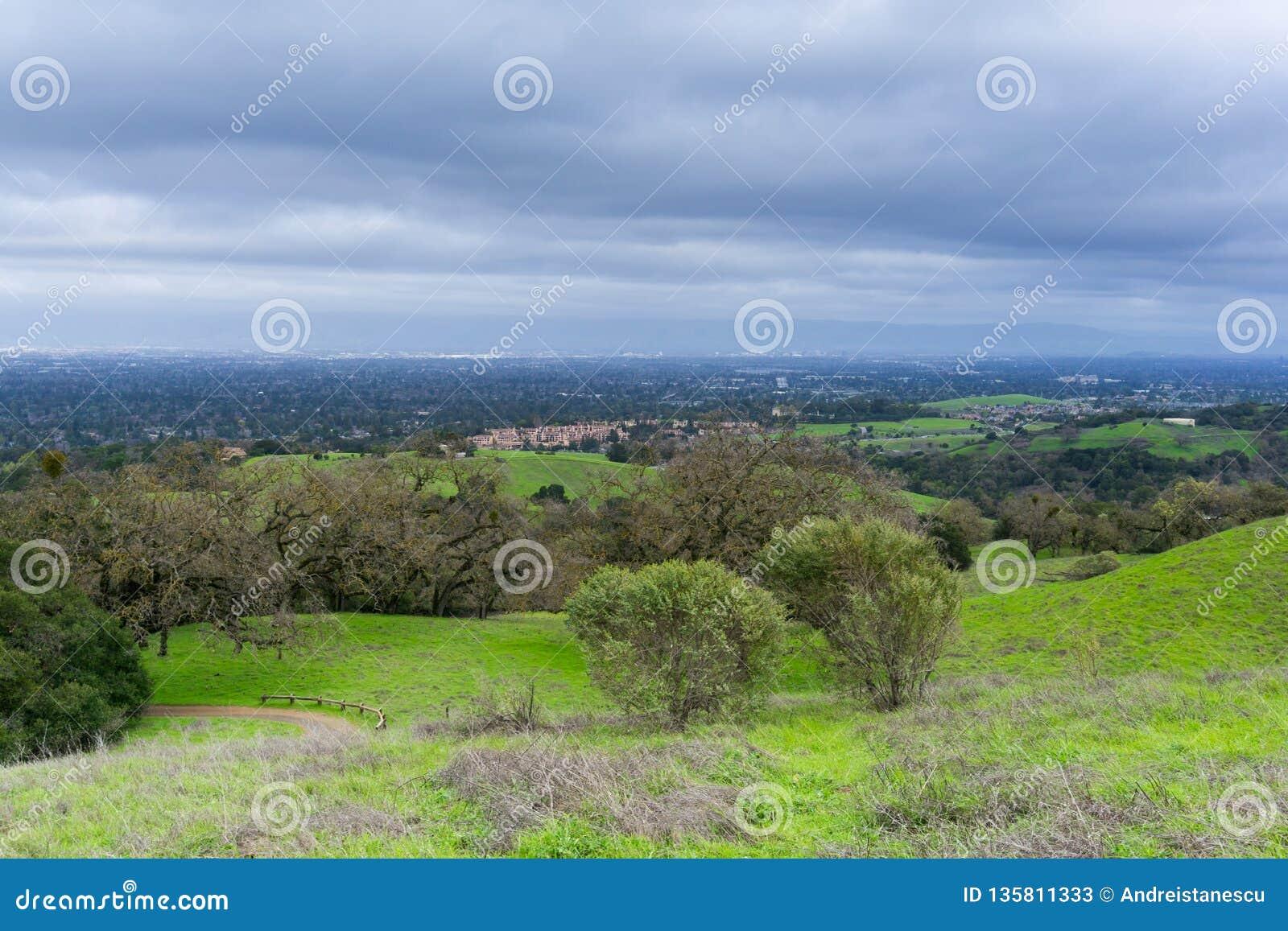 Луг и холмы на пасмурное и дождливый день в парке графства Rancho Сан Антонио; Сан-Хосе и Cupertino на заднем плане, юг Сан