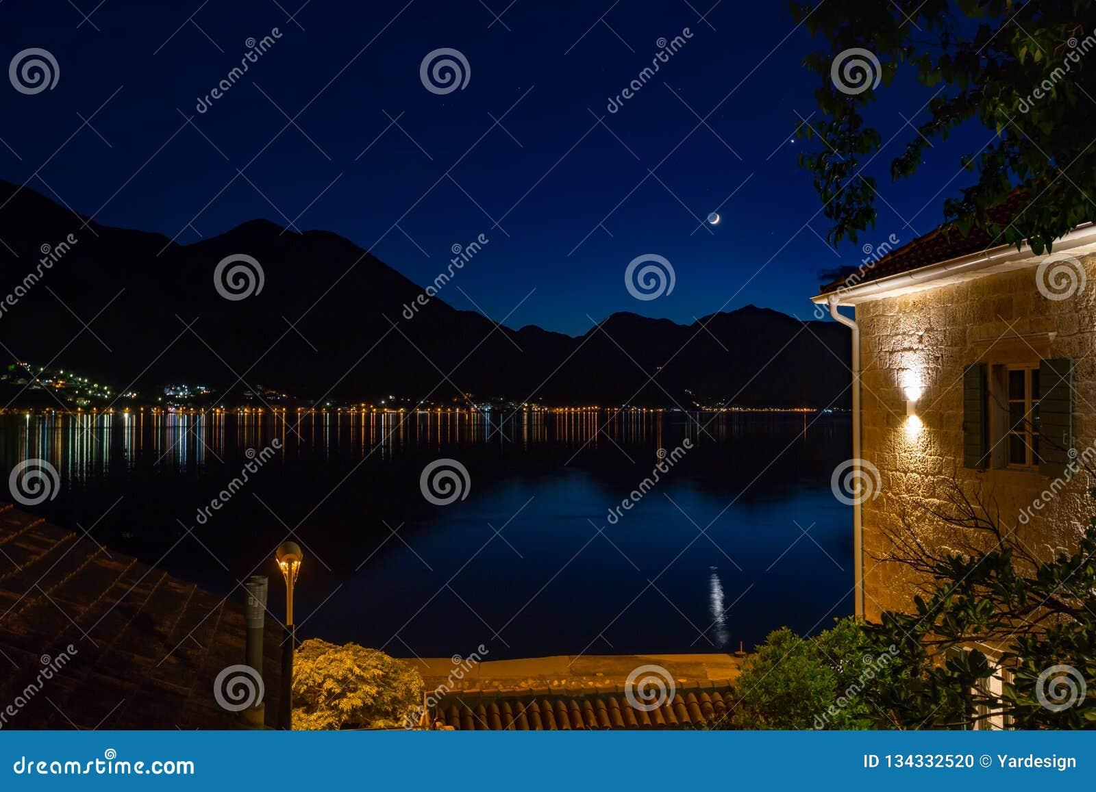 Луна и звезды и электрические света отражая вечером в заливе Kotor, Черногории