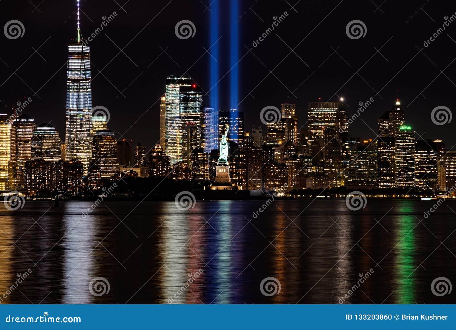 Лучи 9/11 мемориалов с статуей свободы и более низким Манхаттаном