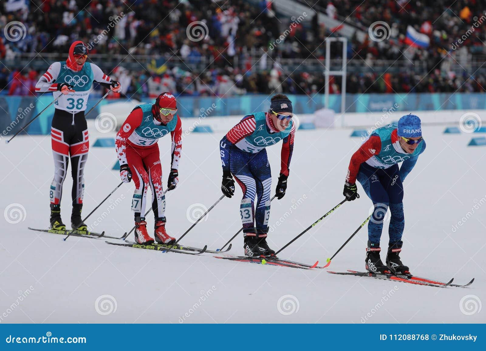 Лыжники состязаются на массовом старте в ` s 15km + 15km Skiathlon людей на 2018 Олимпийских Играх зимы