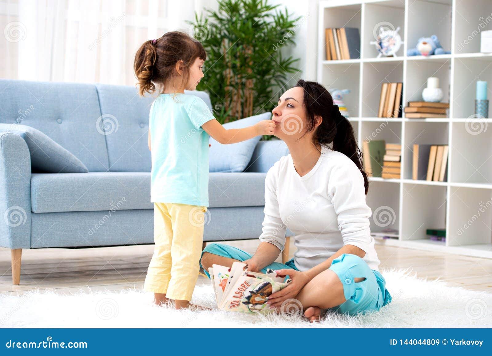 любить семьи счастливый Красивая мать и меньшая дочь имеют потеху, игру в комнате на поле, объятие, улыбку и околпачивают вокруг