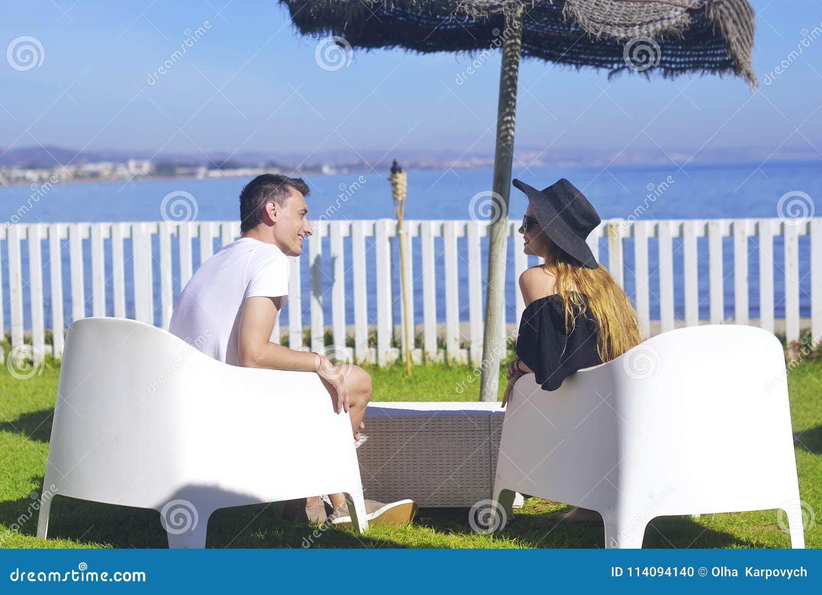 Любовники распологая смотреть в небо и океан, mountion, под зонтик солнца Каникулы, туризм, медовый месяц волосы девушки длинние
