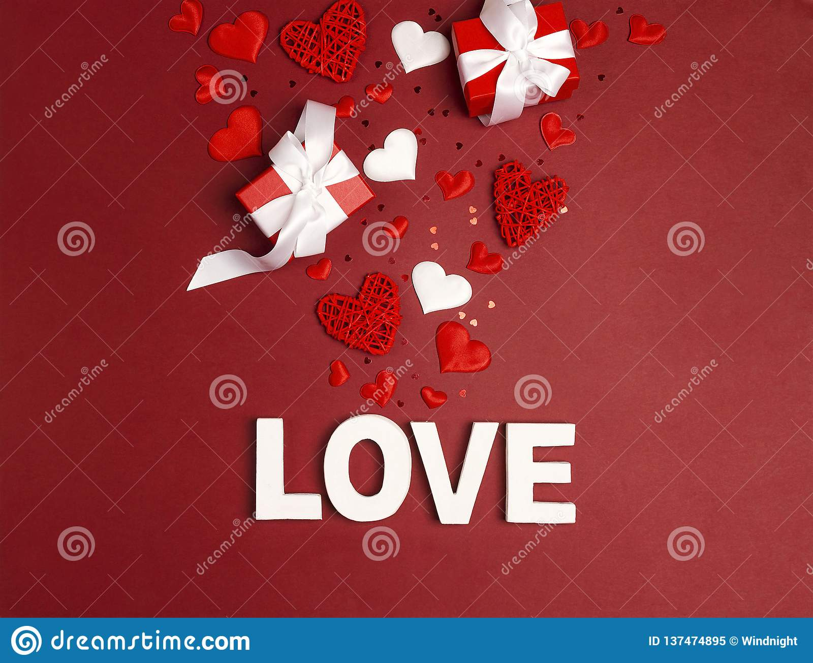 Любовь слова предпосылки дня Святого Валентина St, подарки и декоративные сердца на красном цвете