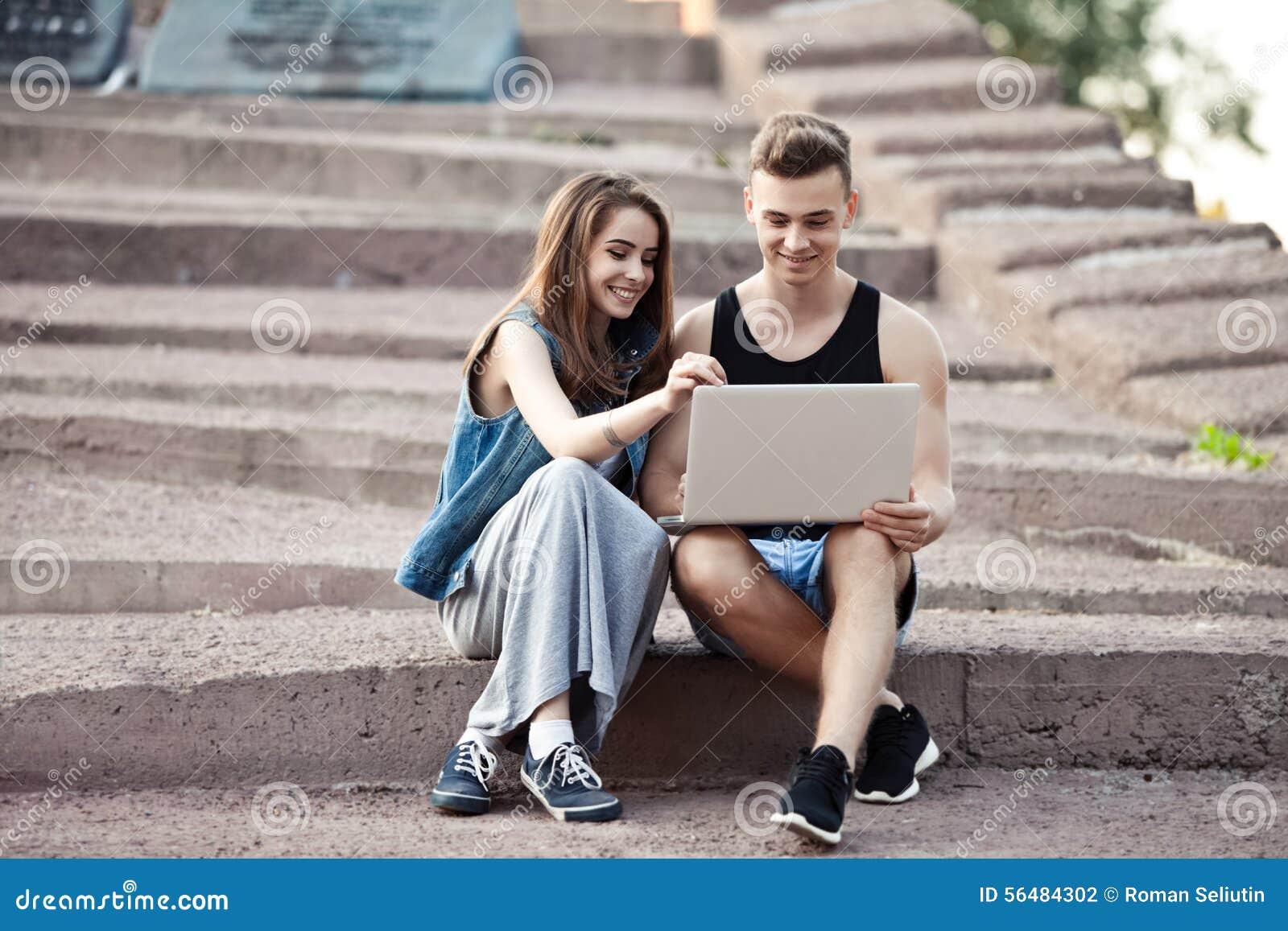 Любящие молодые пары сидя на прогулке с компьтер-книжкой
