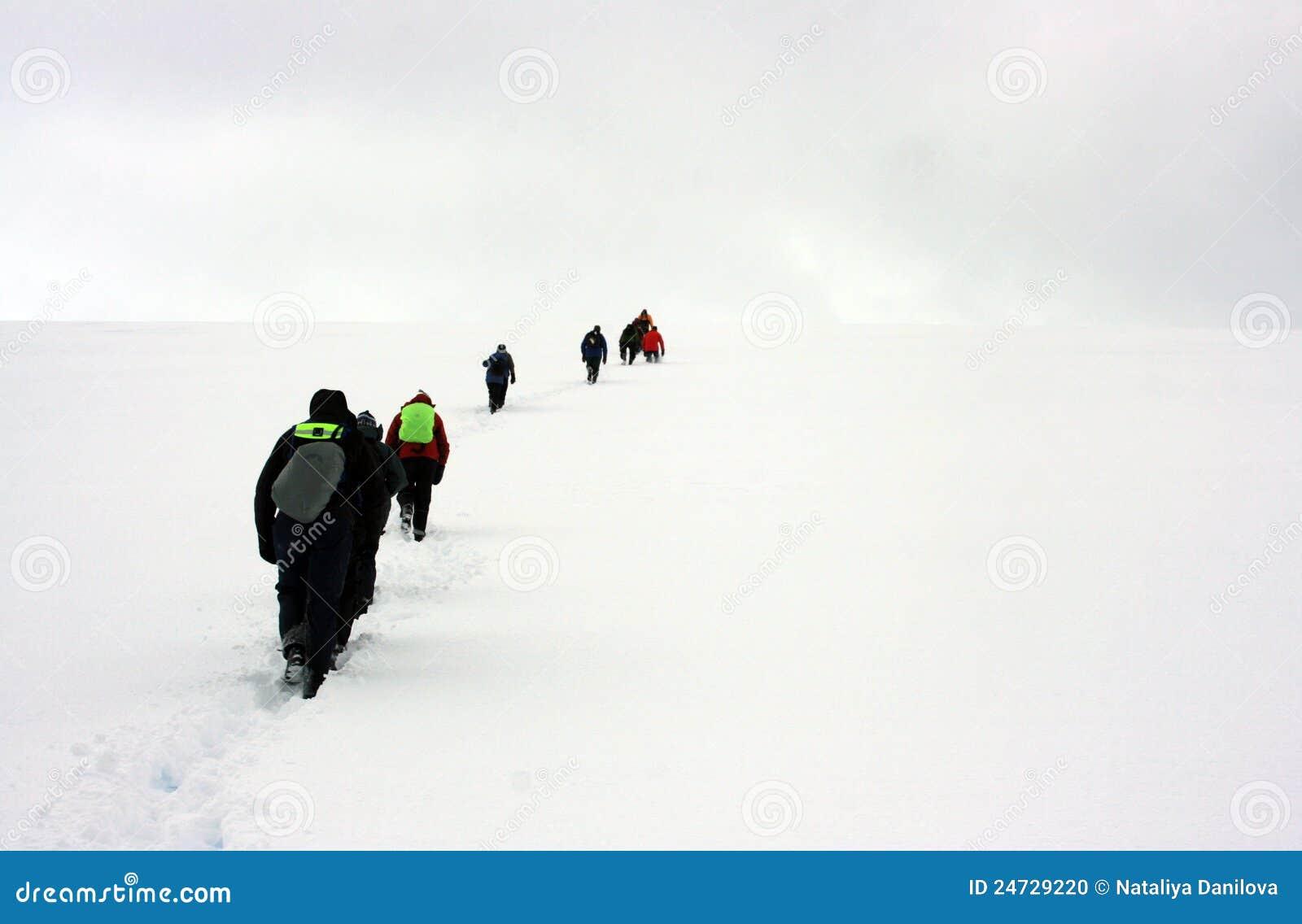 Люди гуляя к горизонту снежка