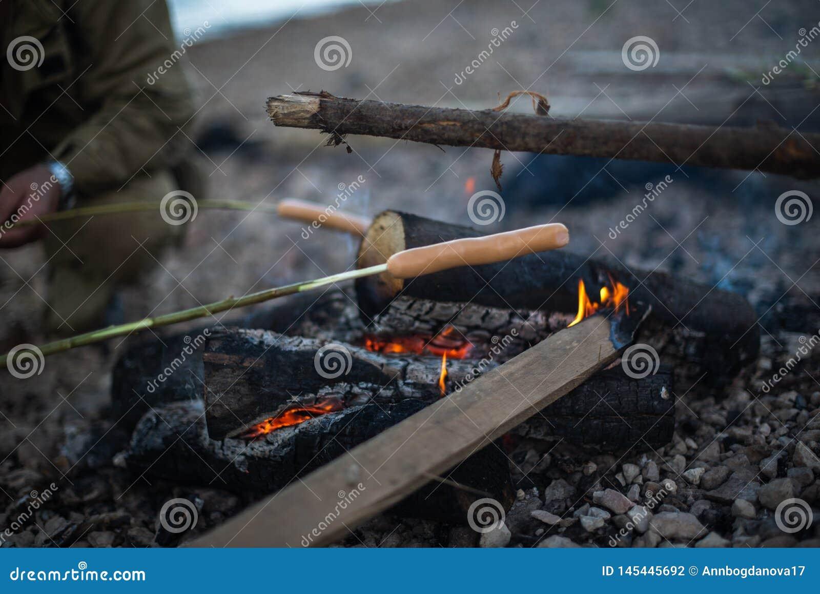 Люди жарят сосиски на открытом огне