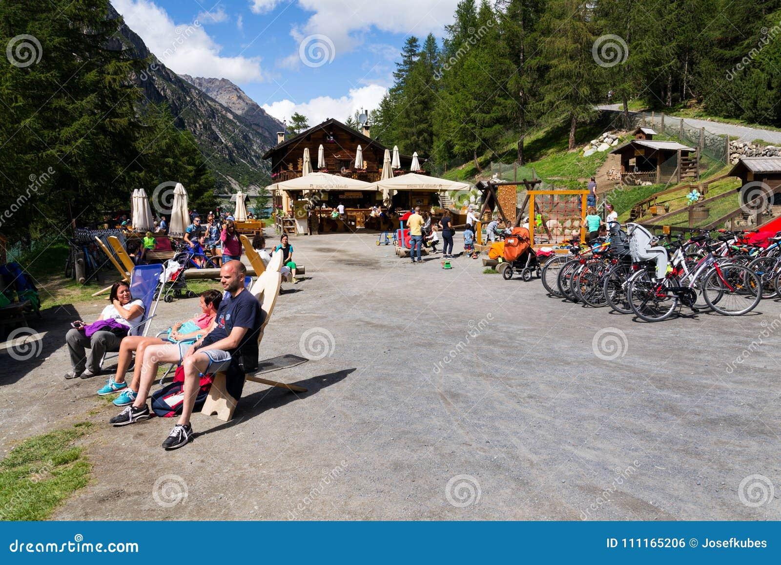 Люди загорая перед рестораном с играть детей и велосипедов на банке Lago di Livigno в Livigno, Италии