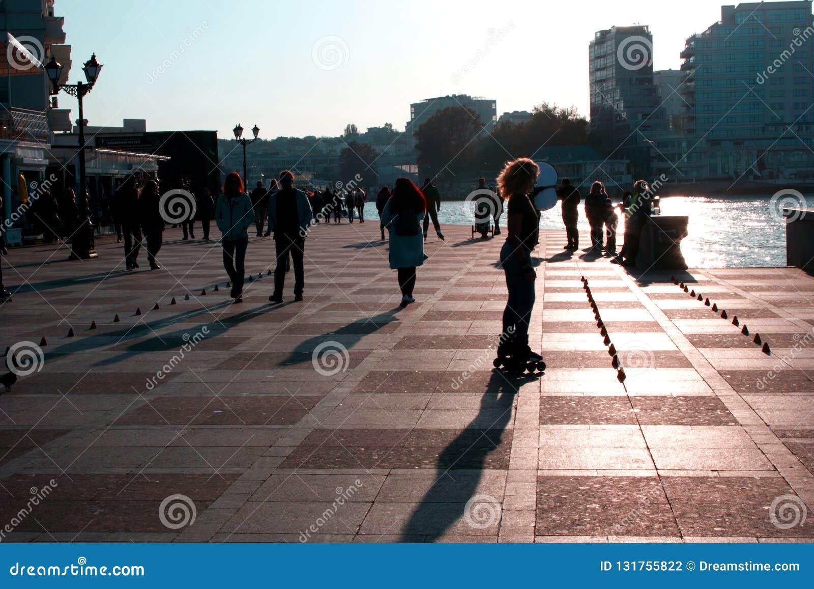 Люди идут вдоль прогулки в городе моря на заходе солнца