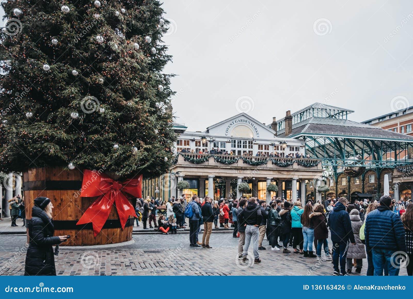 Люди идя гигантской рождественской елкой в рынке Ковент Гардена, Лондоне, Великобритании
