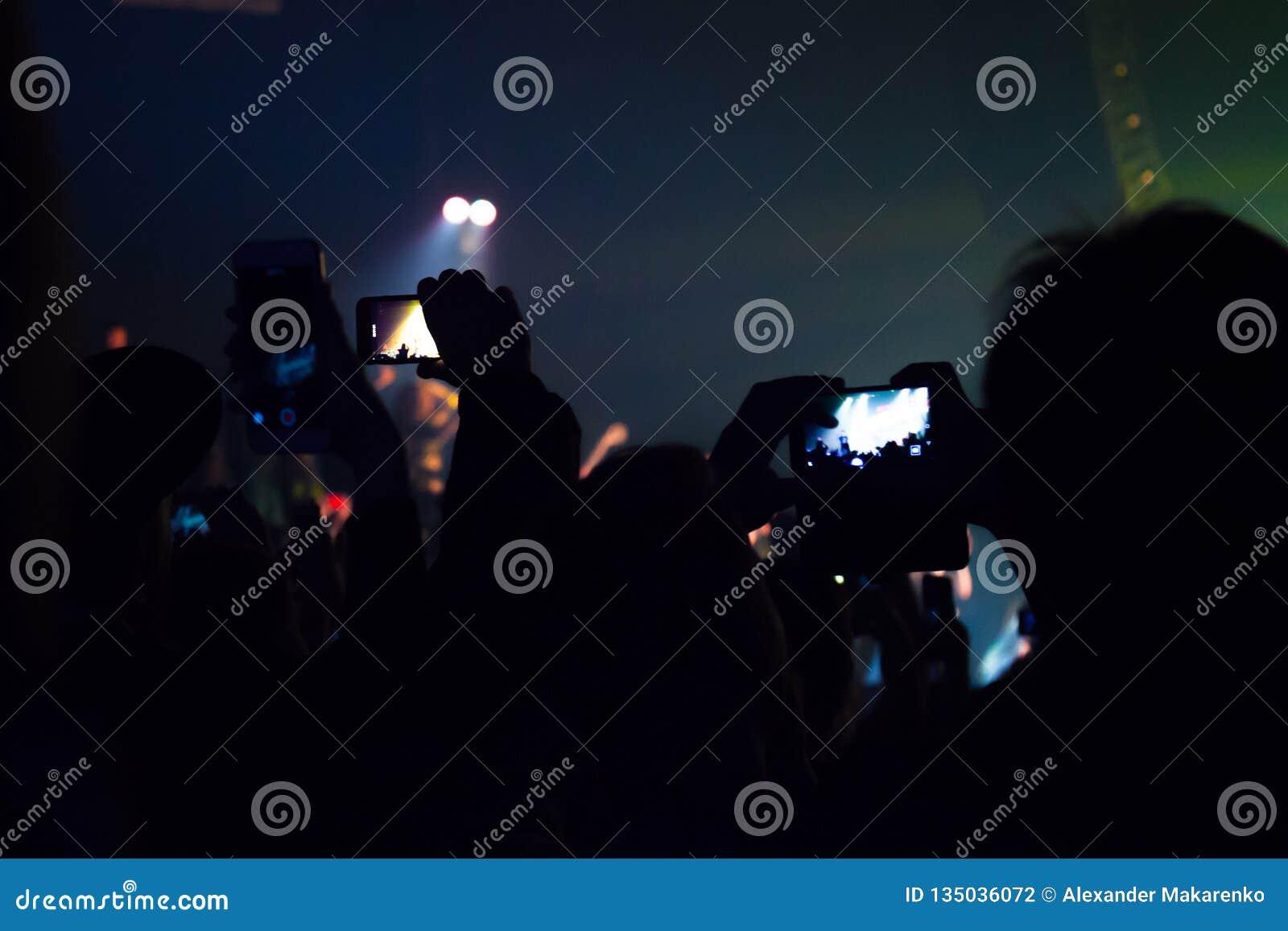 Люди наблюдая концерт и кто-то фото и видео стрельбы с мобильным телефоном