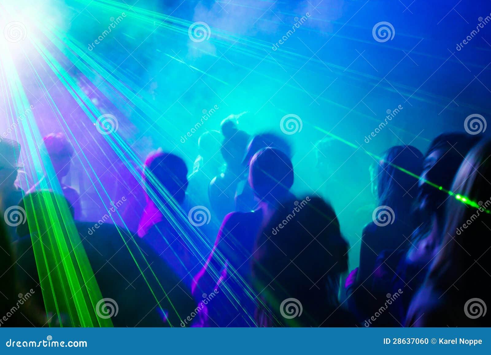 Люди партии танцуя под лазерным лучом.