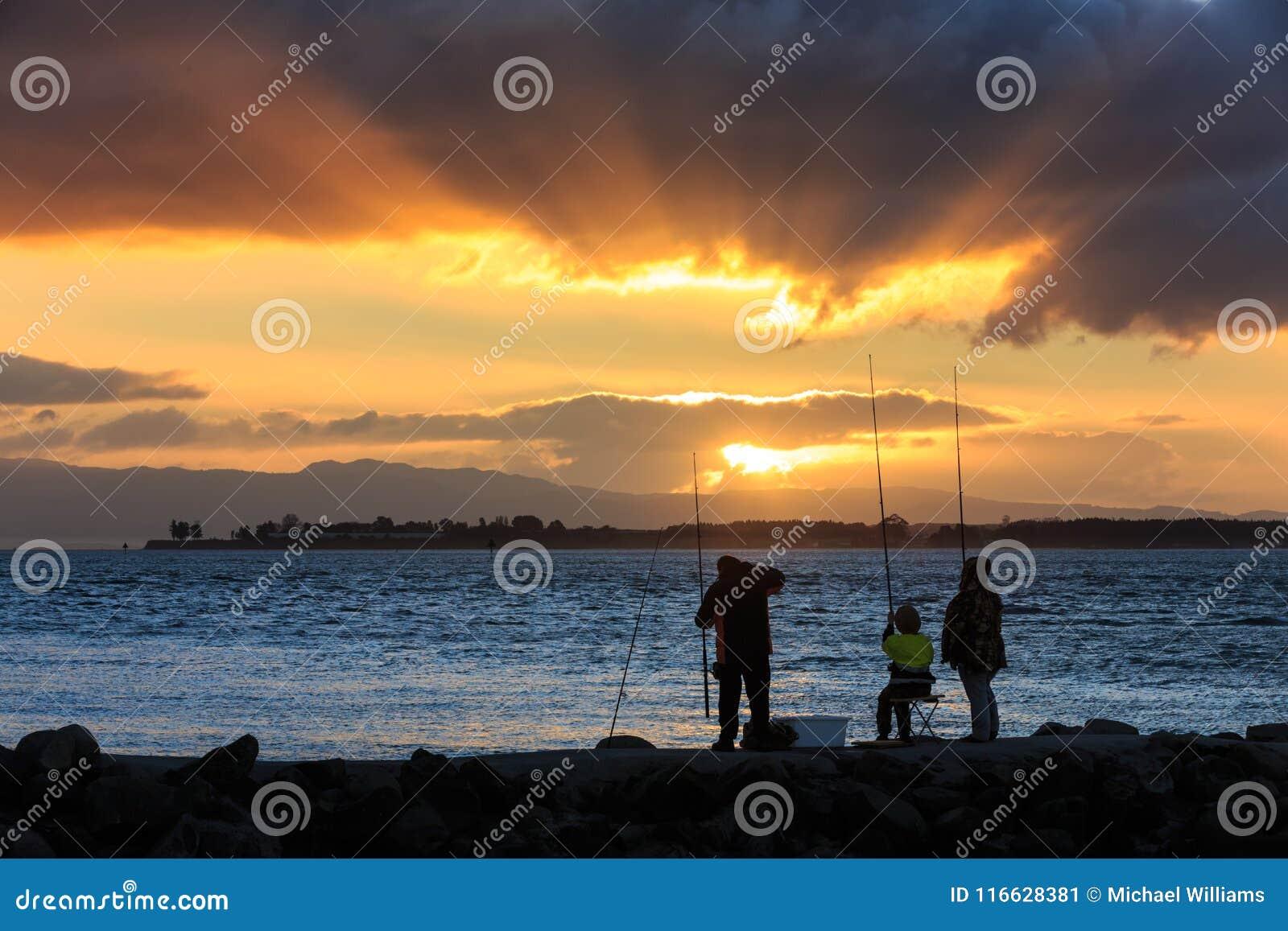 Люди удя на заходе солнца, с солнечными лучами через облака